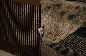 A migrant looks down as he stands atop of the USA/Mexico border fence moments before jumping over the U.S. border from Tijuana, Mexico, on 28 December 2018.