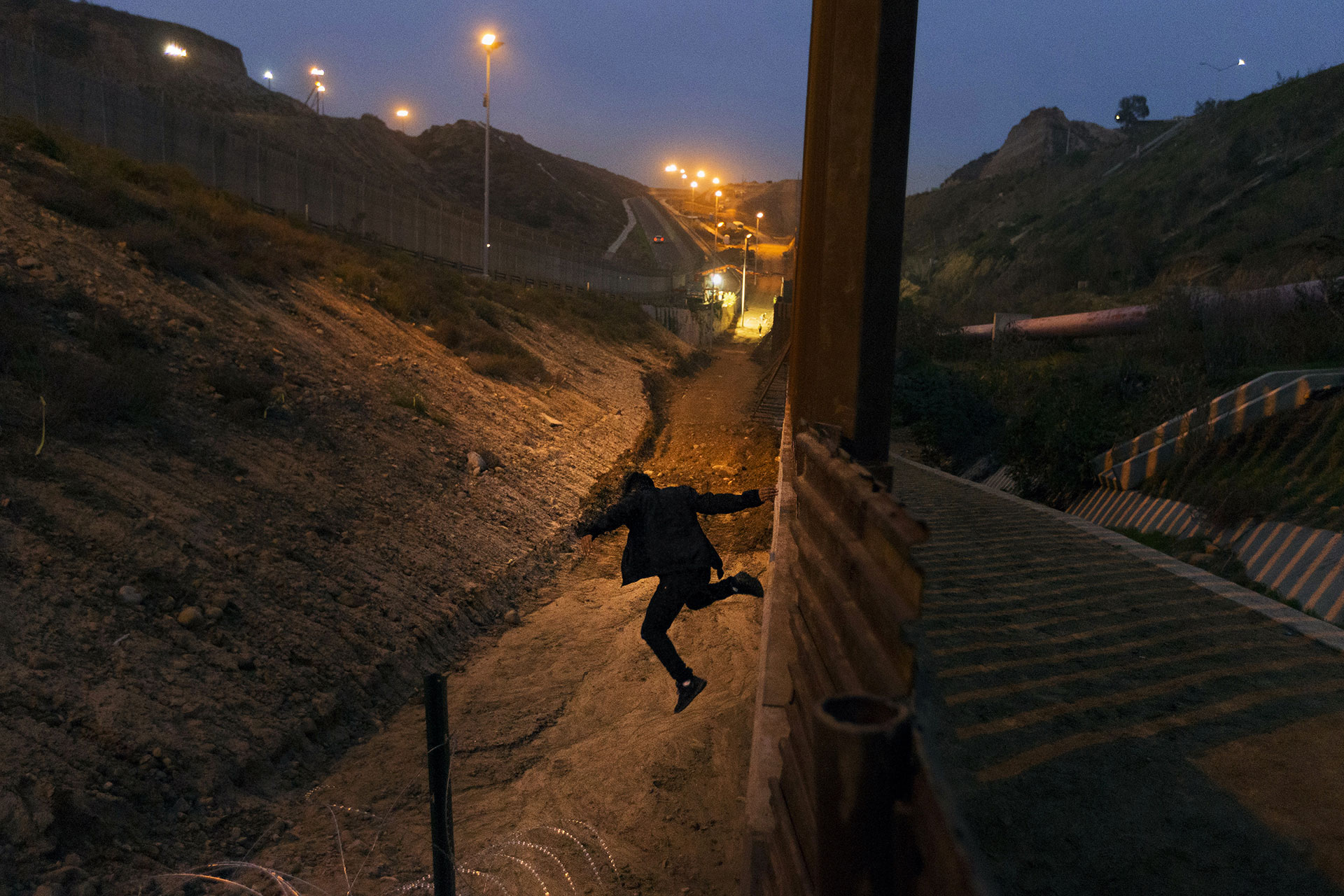 A Honduran migrant jumps from the U.S. border fence in Tijuana, Mexico on 21 December 2018.