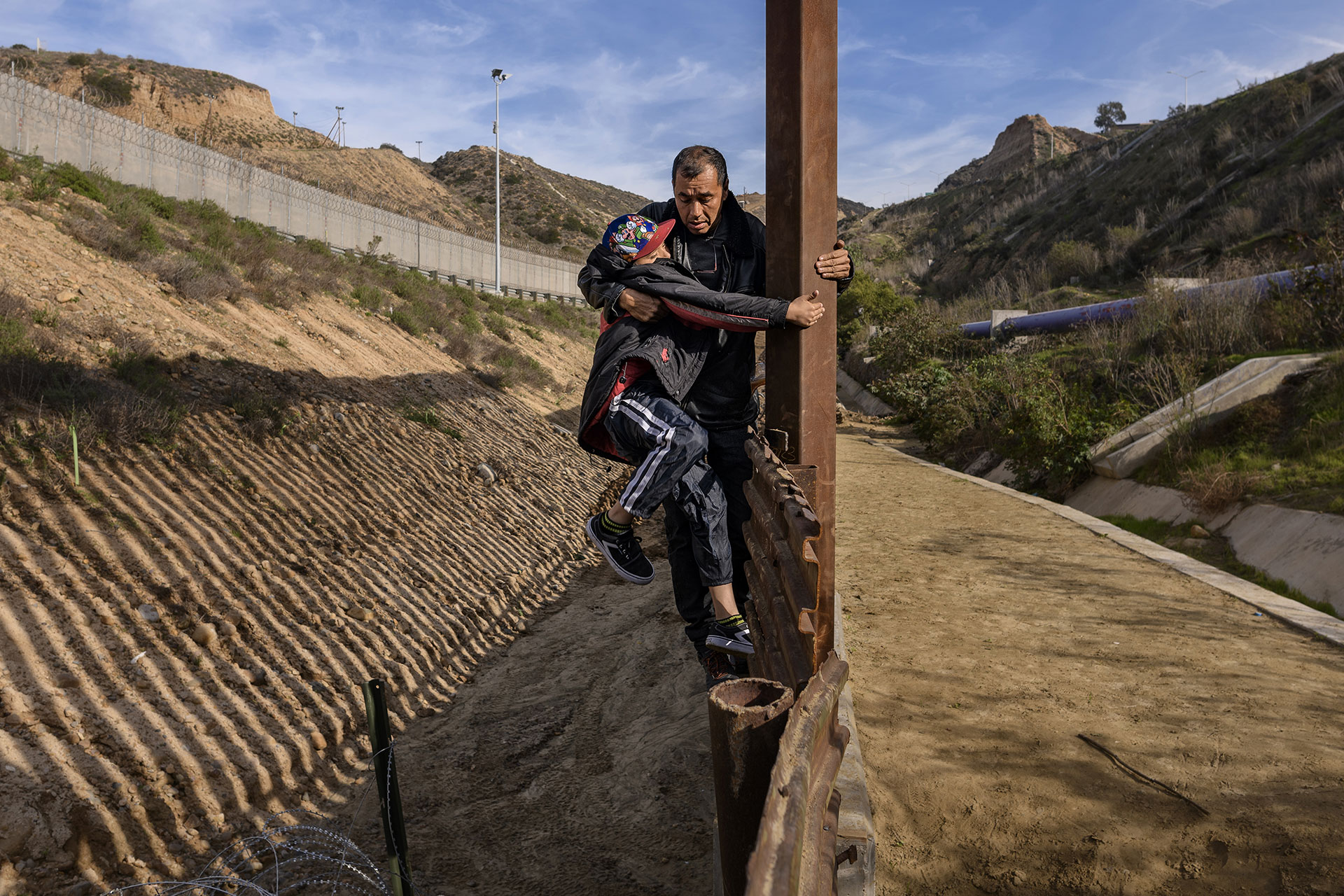 A man holds his son while they scale the U.S. border fence before jumping from Tijuana, Mexico on 22 December 2018.