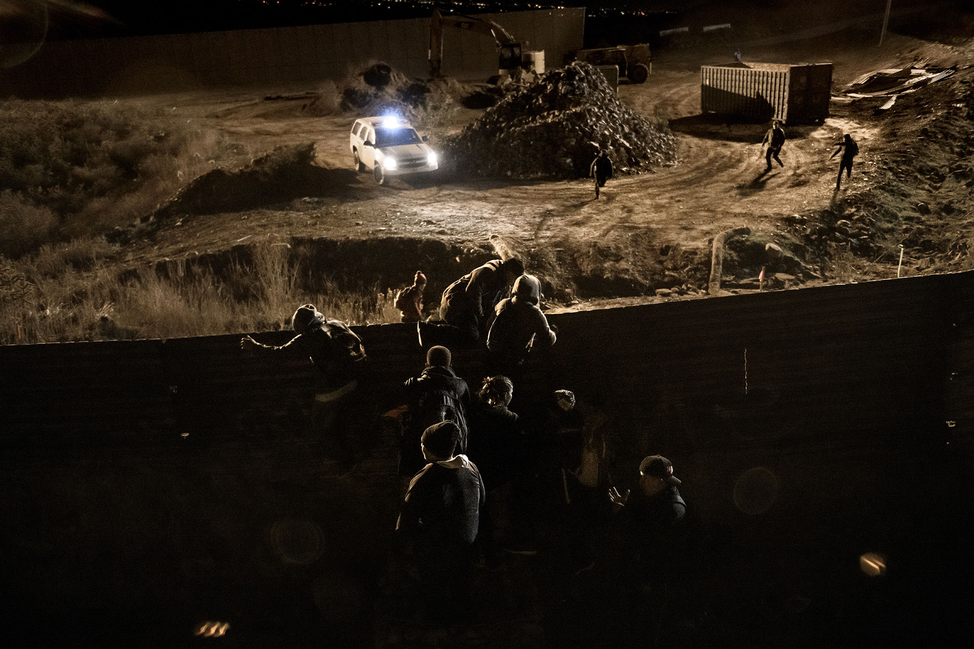 This picture, taken from Tijuana on 25 December 2018, shows how several migrants jump over the border wall while a U.S. Border Patrol official is unable to stop them.