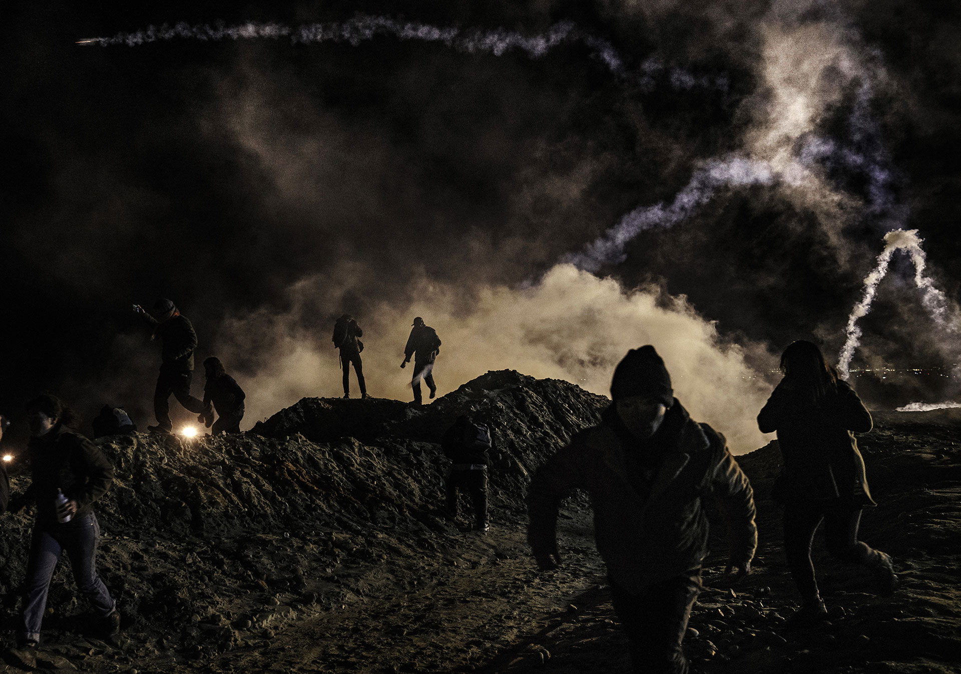 Migrants on the Mexican side of the wall in Tijuana run from teargas shot by U.S. Border Protection on 1 January 2019.