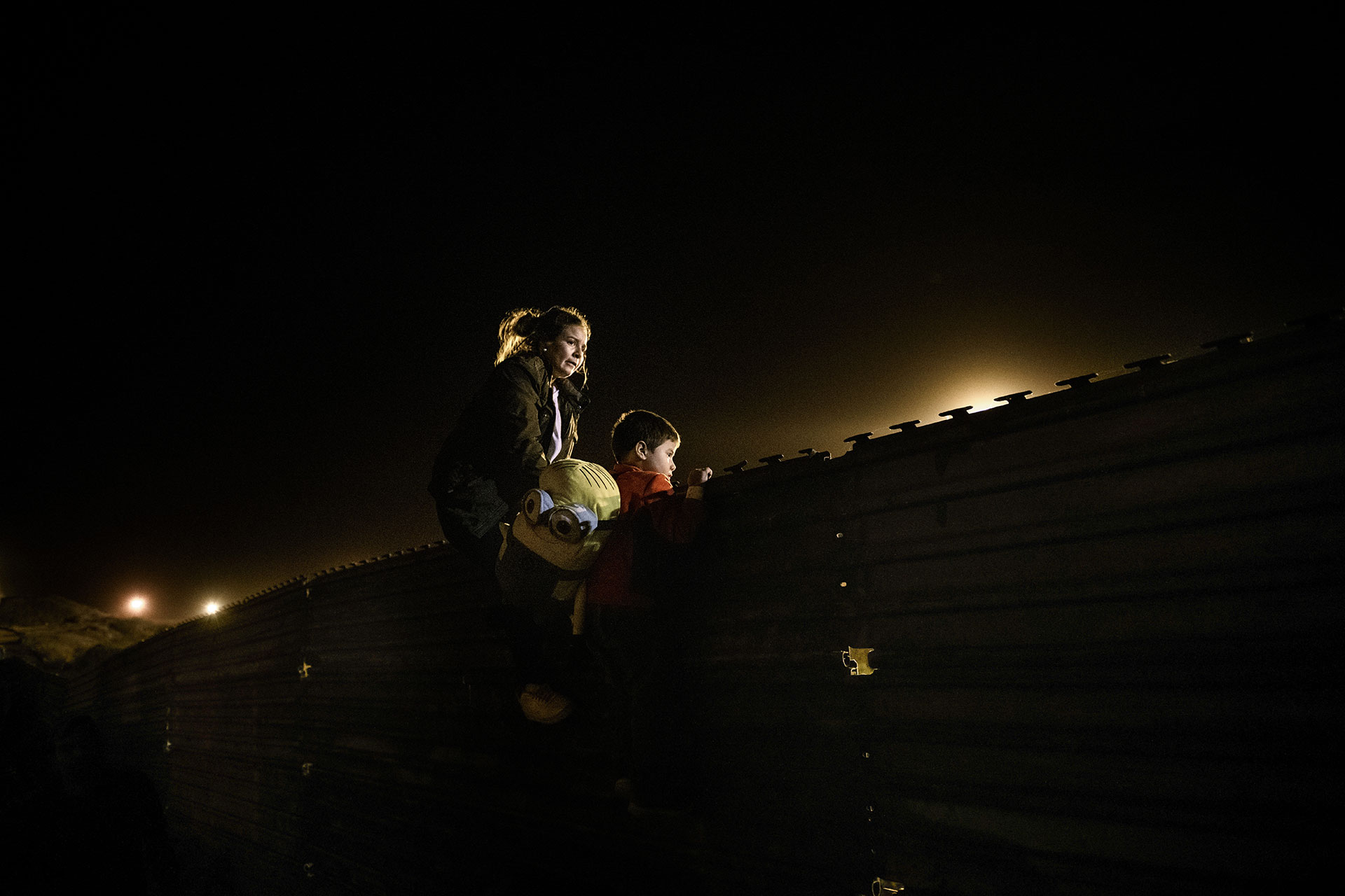 A Honduran mother and her son scale the wall to jump over to the U.S. from Tijuana on 26 December 2018.