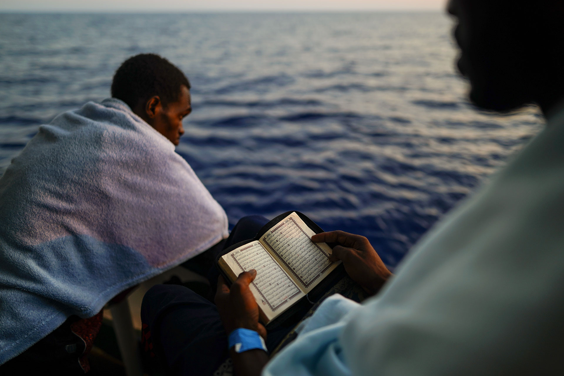 A young man reads the Koran aboard the rescue ship of the NGO Proactiva Open Arms in the central Mediterranean Sea on 3 August 2018.