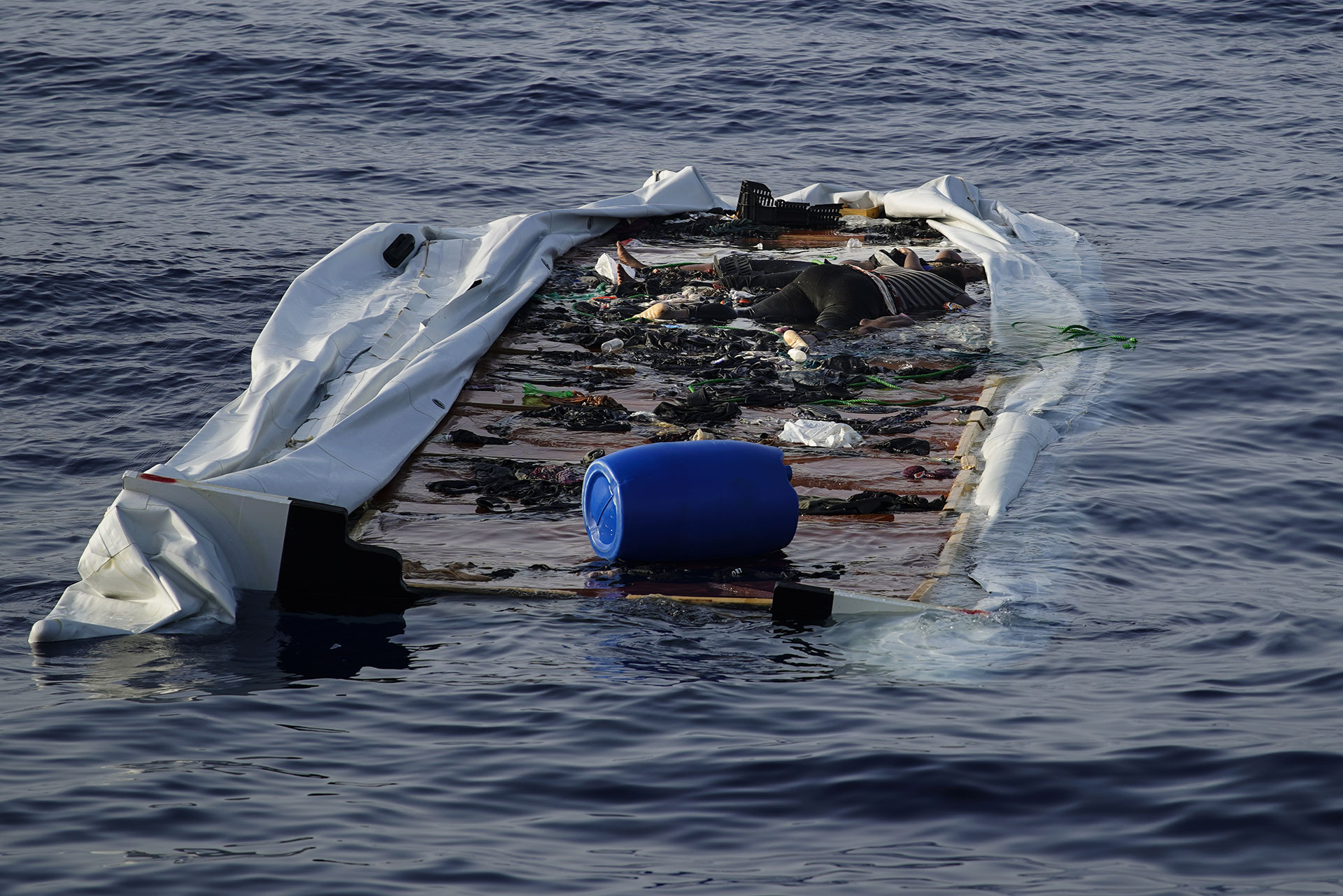 Josepha, the only survivor, alongside the bodies of a young boy and a woman in an abandoned dinghy floating in the central Mediterranean Sea, 17 July 2018.