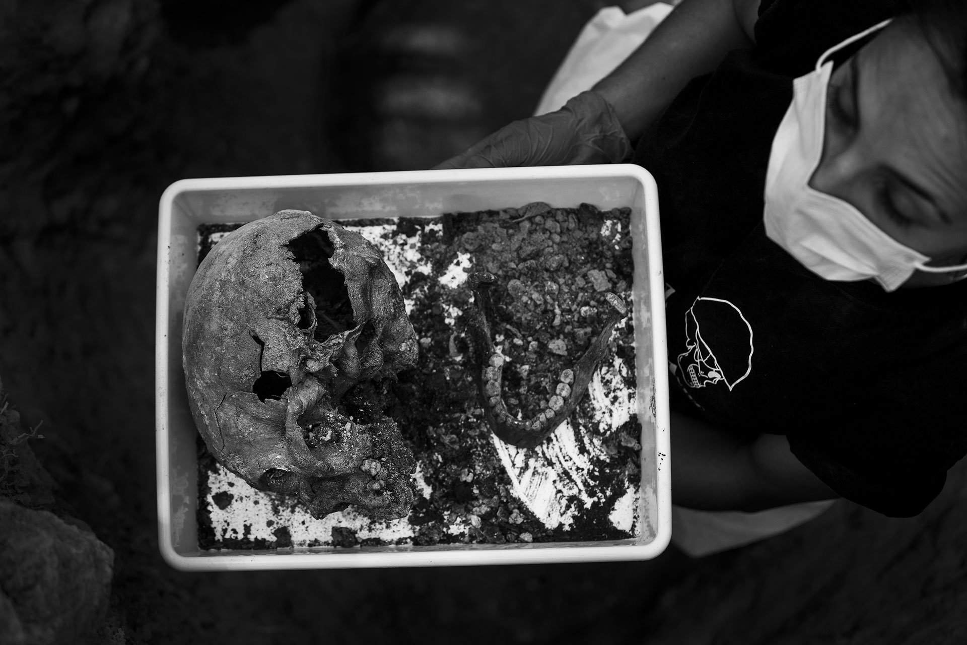Una forense sostiene un cráneo con un impacto de bala encontrado en la fosa 113 del cementerio de Paterna, Valencia, en junio de 2017.