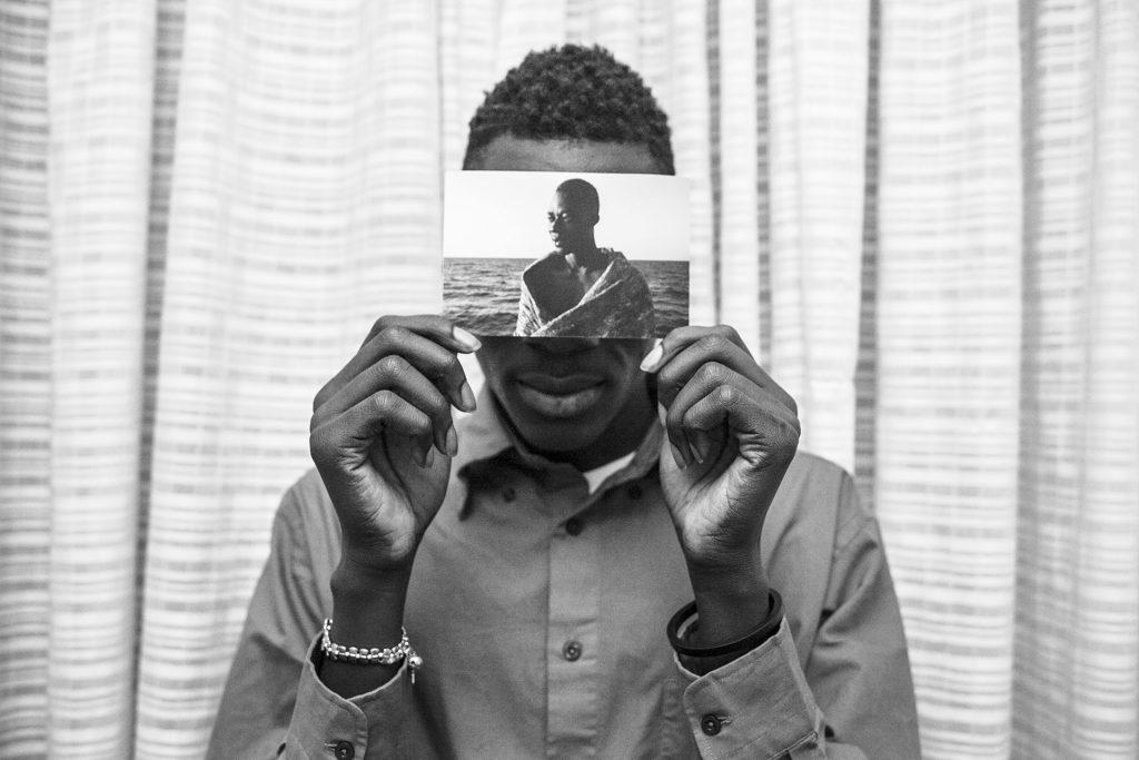 Malick posa para un retrato dentro de su habitación del Hotel Colibri, sosteniendo una foto suya tomada el 2 de agosto de 2016, minutos después de ser rescatado de las aguas del Mediterráneo. Sobrevivió después de siete horas de viaje desde la salida de la costa de Libia, viajando en un bote de goma con 120 personas a bordo.