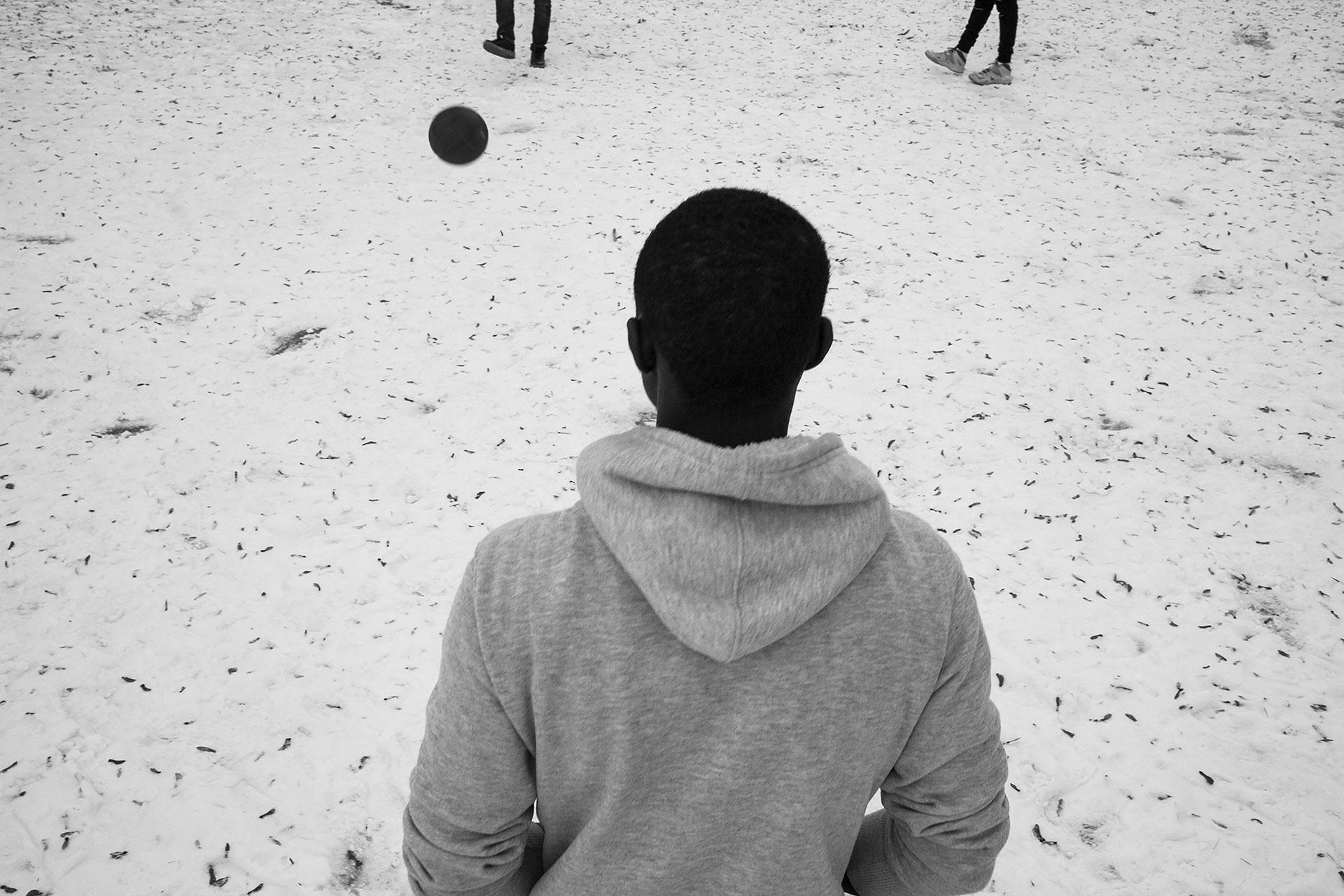 Baba, de Senegal, juega al fútbol con Malick, de Gambia, y Mohammed, de Malí, en un parque cubierto de nieve cercano al centro donde viven. Malick, al igual que otros compañeros, vio la nieve por primera vez durante el invierno de 2017.