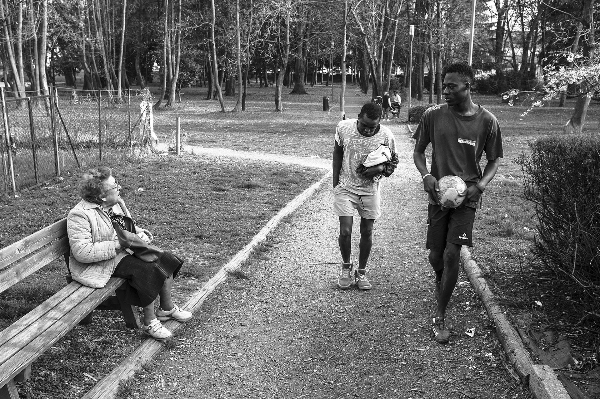 Malick y Muhammad, de Senegal, regresan a casa después de jugar al fútbol en un parque situado cerca del lugar donde viven. Este parque es frecuentado también por ancianos que residen en los edificios aledaños, que ahora conviven con la realidad migratoria. Biella tiene una población envejecida, y la mayoría de sus jóvenes se trasladan a ciudades más grandes para continuar sus estudios.