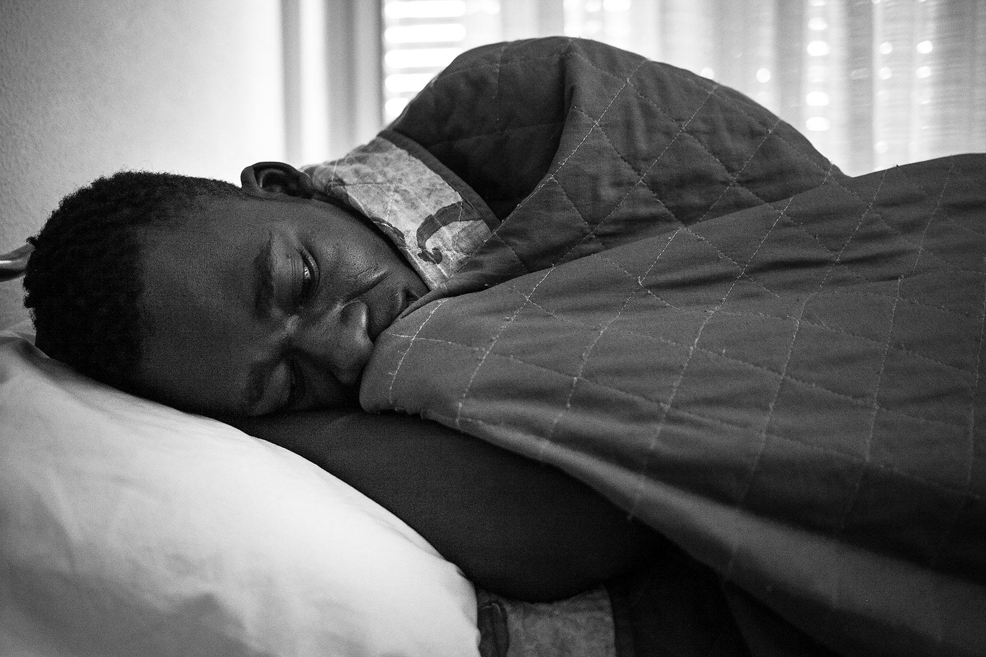 Malick descansa en su cama en el Hotel Colibri. Comparte habitación con tres personas más de Gambia y Senegal.