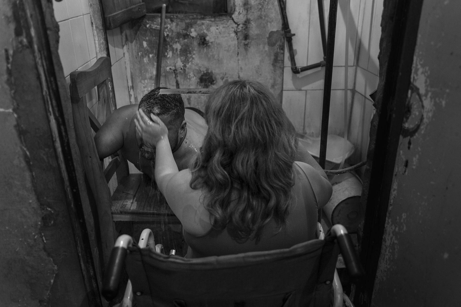 Vero asiste a Jorge en su higiene. Nunca tuvieron asistencia domiciliaria para estos requerimientos, a pesar de haber realizado los trámites en servicios sociales, reciben una pensión mínima que no cubre sus necesidades básicas. Jorge nunca fue reconocido como afectado por Talidomida por parte del Estado Argentino.