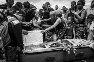 A woman cries at the funeral of her husband, Keiber Cubero, aged 25. As a father struggling to find food for his daughter, Keiber went out one night with others to rob a restaurant but were caught and killed by the police.