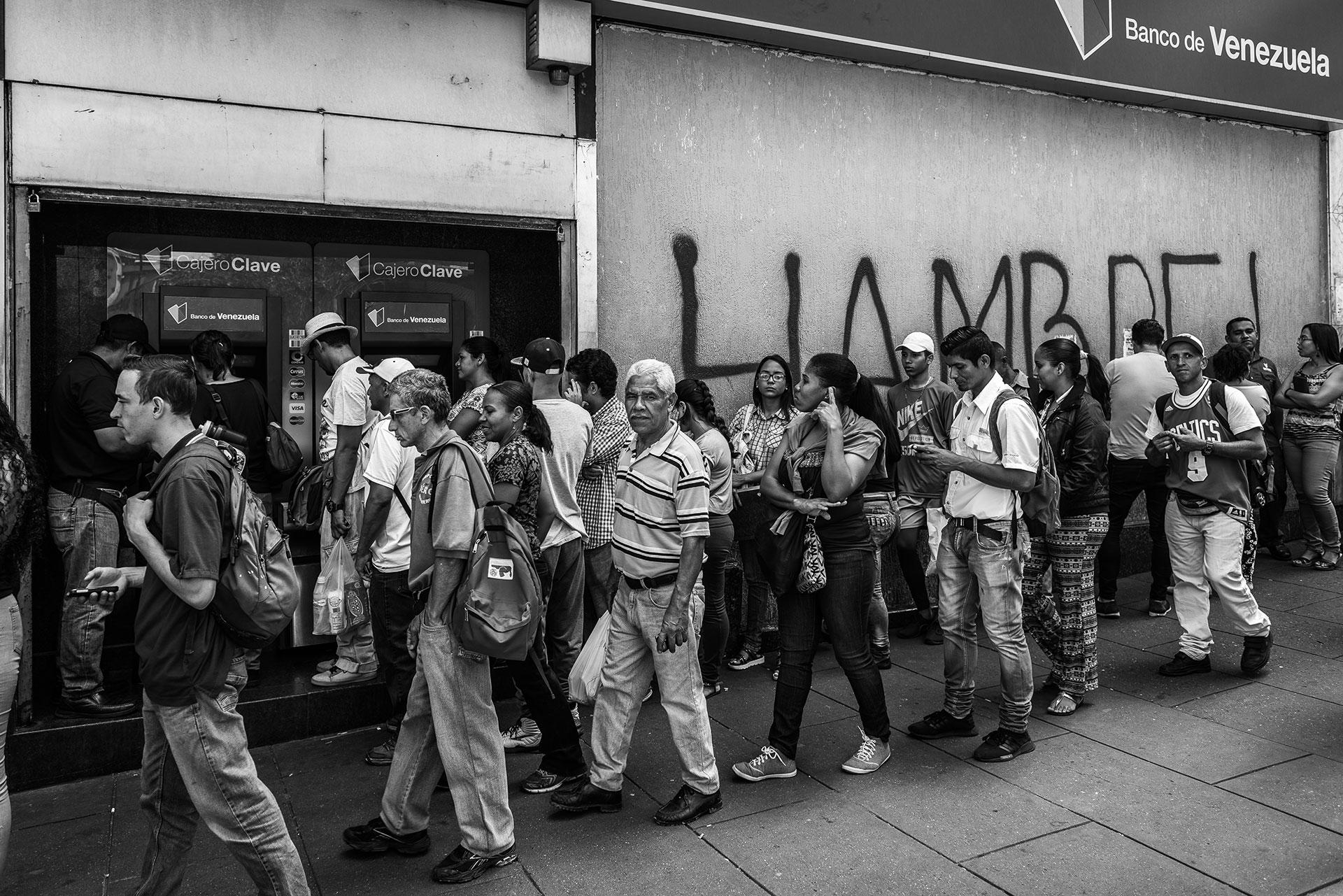 """Un grupo de gente hace cola frente a un banco para retirar efectivo en un cajero automático. Detrás, en un grafiti se lee """"hambre""""."""
