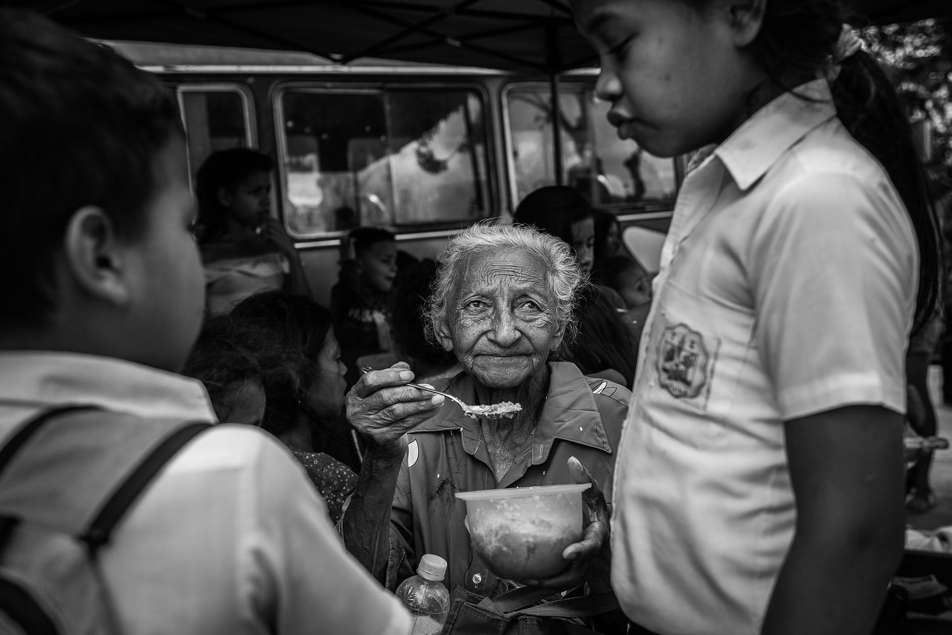Una anciana da de comer a una niña en un comedor social organizado por una ONG local. Según Cáritas, el 65% de los menores con los que han trabajado sufren malnutrición.