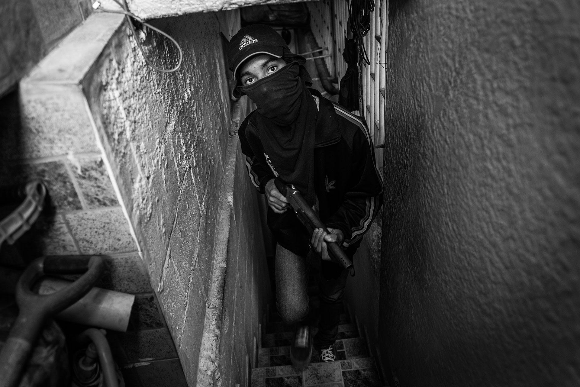 """Freddy (16 años), miembro de una banda de secuestradores, en un """"piso franco"""" en Caracas. Se unió a la banda cuando se dio cuenta de que las cosas eran difíciles en casa. """"Vi a mi mamá que luchaba para comprar harina, arroz, cualquier cosa. Ahí es cuando decidí unirme a la banda, para poder comprar algo de comida para mis hermanos pequeños. Empecé como un ladrón pero ahora me han dado un arma para participar también en secuestros"""", explica."""