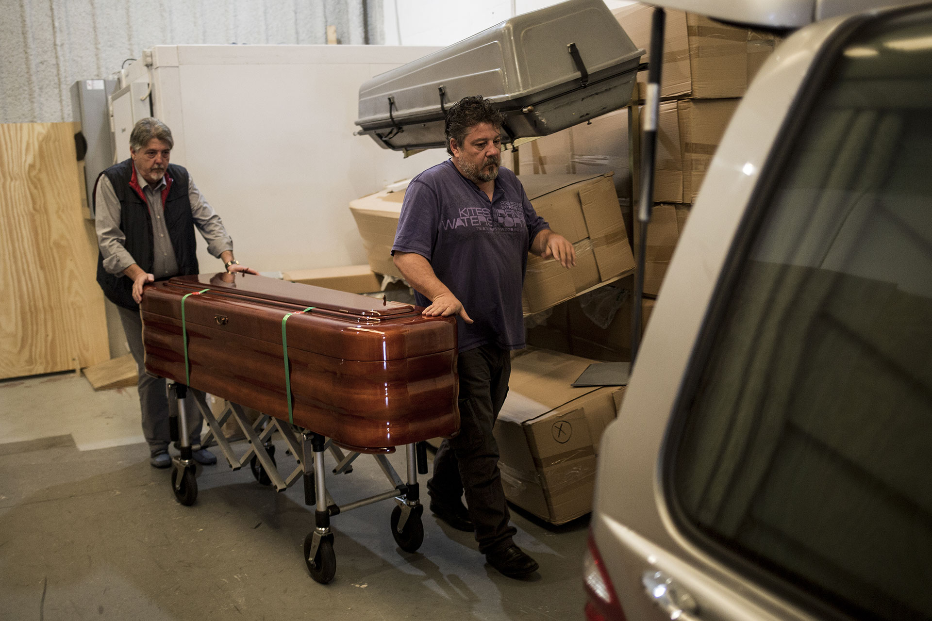 Martín Zamora and a colleague push the coffin carrying the corpse of Zohra Sarrouj at the Southern Funeral Assistance premises in Algeciras, Spain.