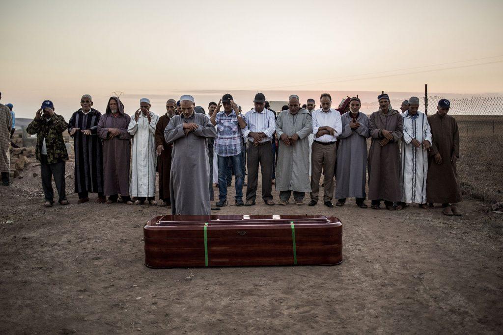 Men stand praying moments before Zohra Sarrouj's burial.