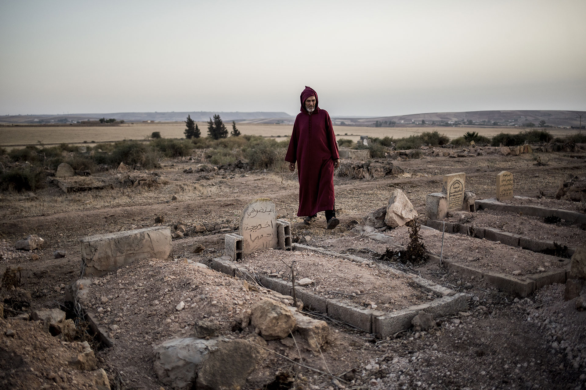 A man stands between tombs moments before the burial.