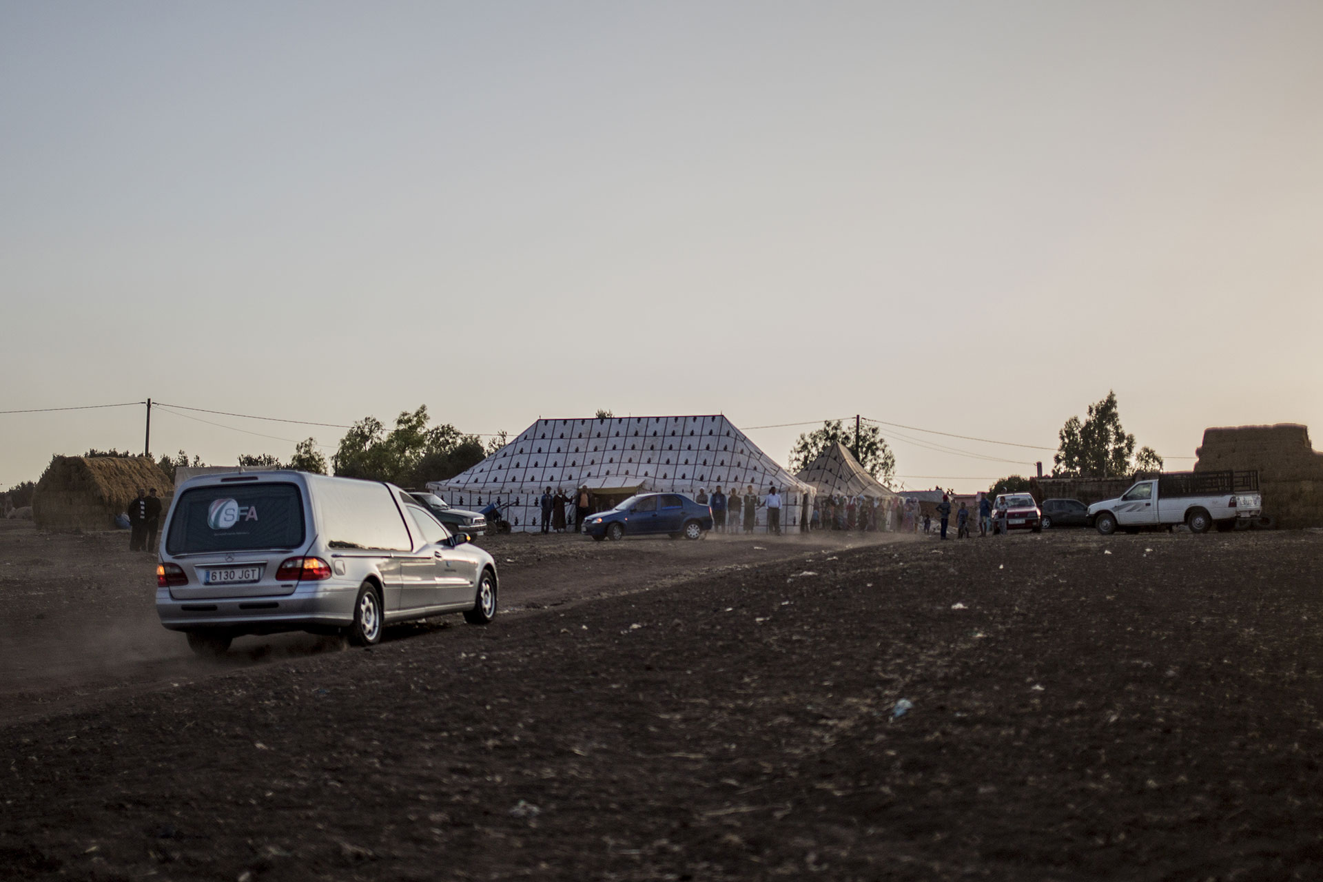 The hearse carrying Zohra Sarrouj's corpse approaches the family farm where family and friends are waiting.
