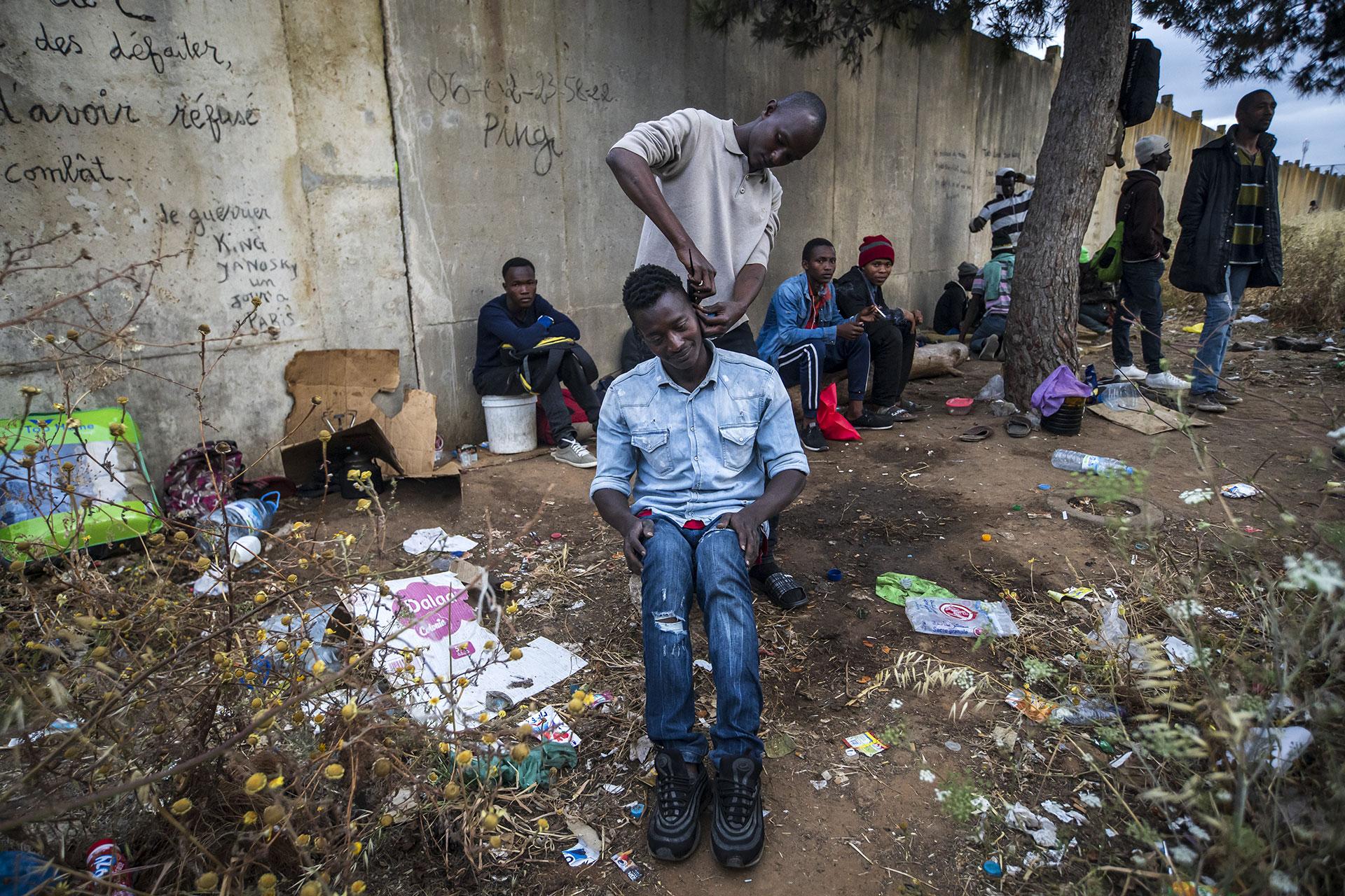 Un joven le corta el cabello a un compañero en un parque de Rabat, mientras esperan para intentar cruzar a Europa, 24 de Mayo de 2019.