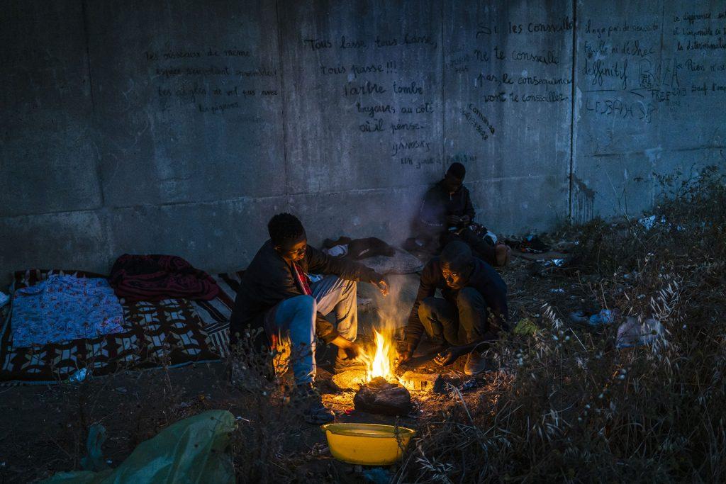 Unos jóvenes encienden una hoguera para calentar un poco de comida en un parque de Rabat, 24 de Mayo de 2019.