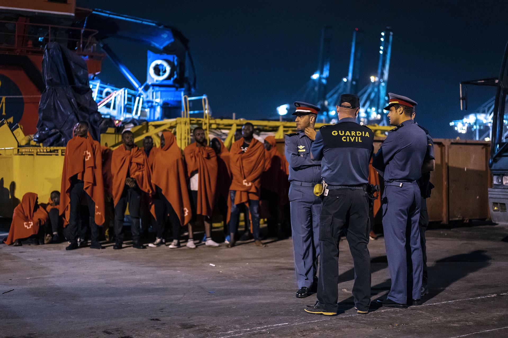Algunas de las personas que fueron interceptadas por un barco de Salvamento Marítimo cuando intentaban llegar a la costa a bordo de un pequeño, esperan en el puerto de Algeciras cerca de una patrulla conjunta de Guardia Civil y Gendarmería Marroquí, 21 de Julio de 2019.