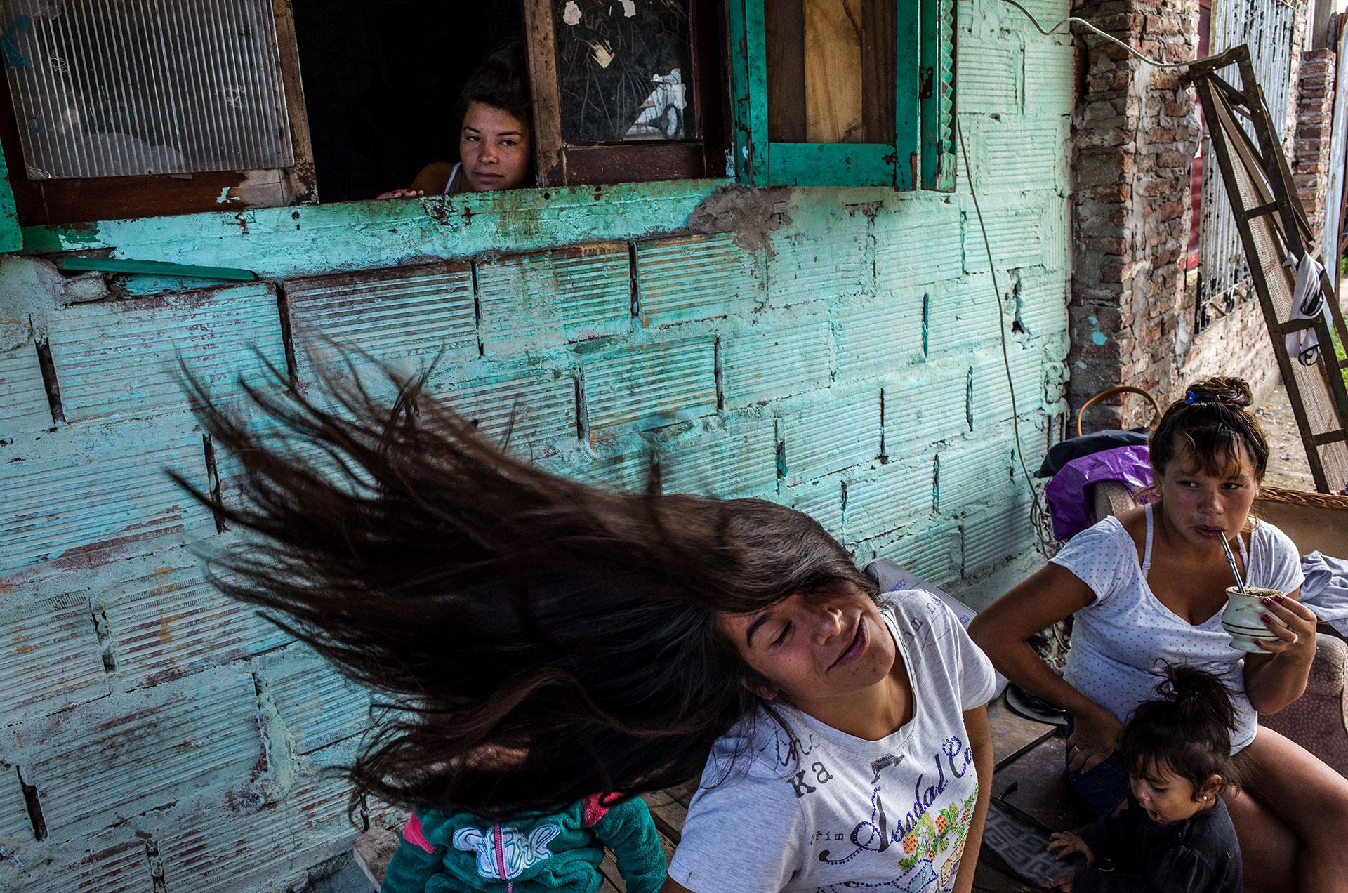 Maira Giménez, de 19 años, frente a la casa de su tía con sus primos. Cuando tenía 5 años, su padrastro comenzó a maltratarla y a golpear a sus hermanos. Después de la muerte de su madre, su hermano comenzó a consumir la droga Paco. Fue asesinado por un oficial de policía. En 2016 Maira perdió su hogar debido a un incendio.