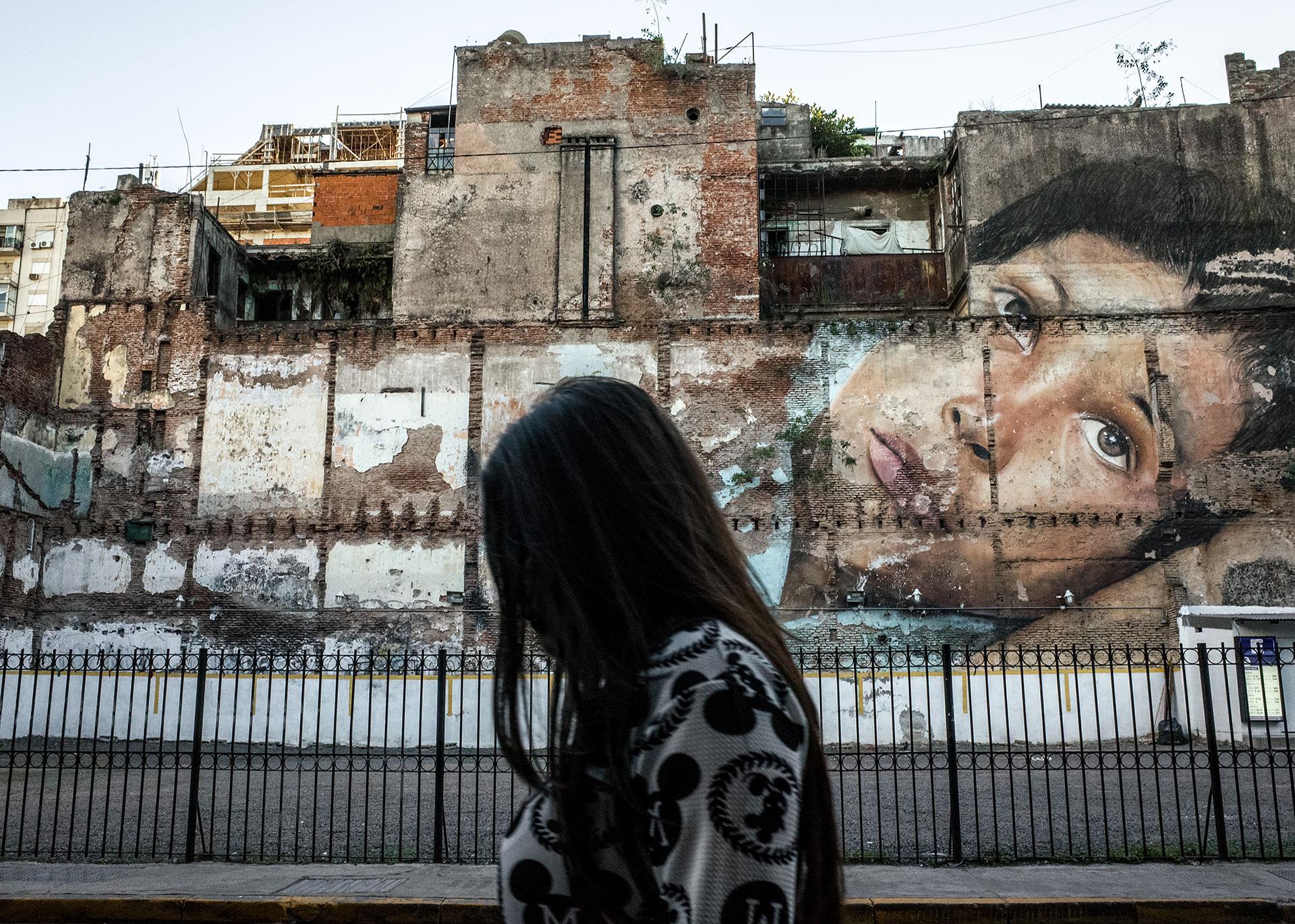 Buenos Aires. Una mujer camina en una calle del centro con un gran mural al fondo. Toda la ciudad está llena de paredes pintadas, a veces edificios enteros o calles. A menudo estas pinturas son políticas, muchas están en contra de la violencia de género, la injusticia y las personas desaparecidas.