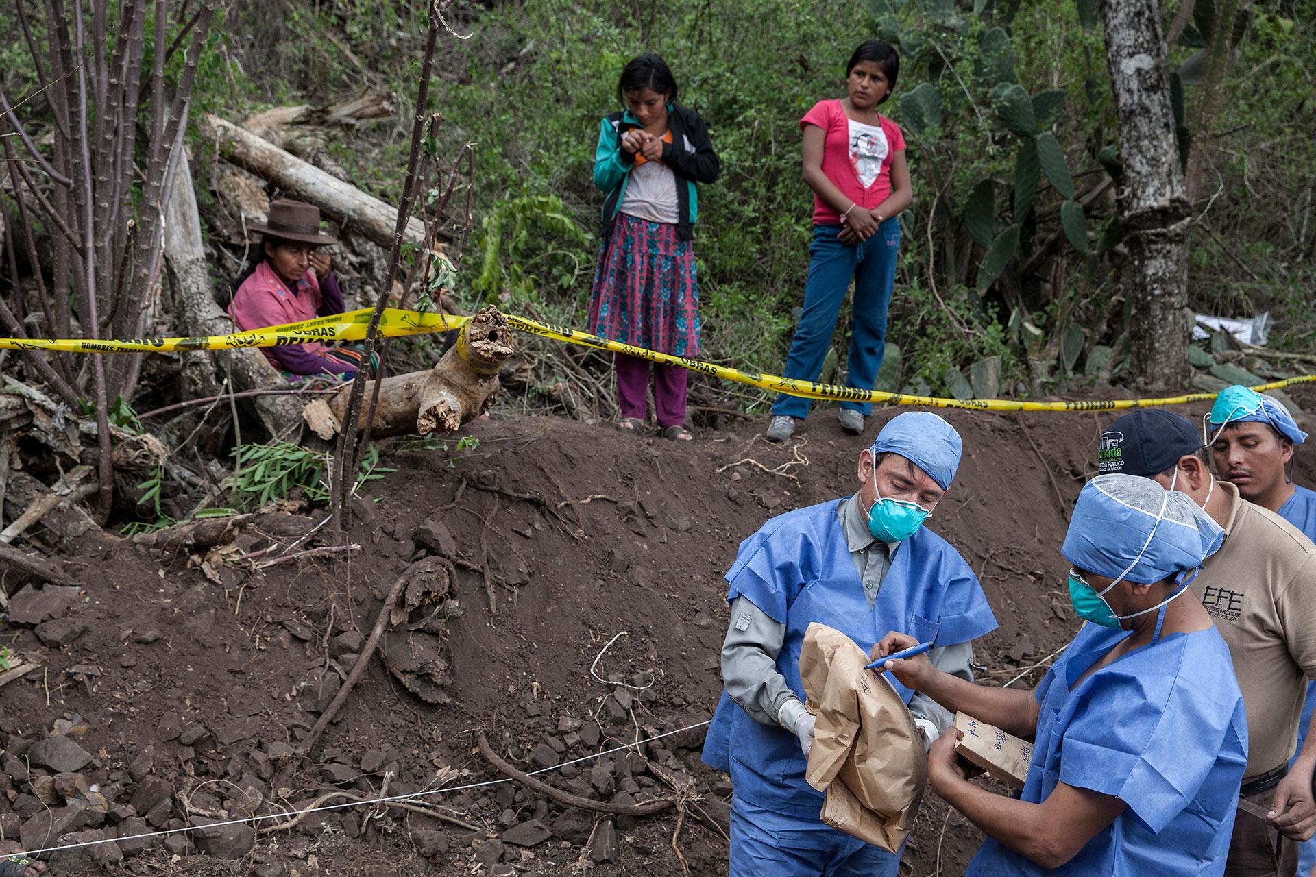 Forenses empaquetan de manera codificada los restos hallados, mientras las familias de las víctimas observan tras la línea amarilla.