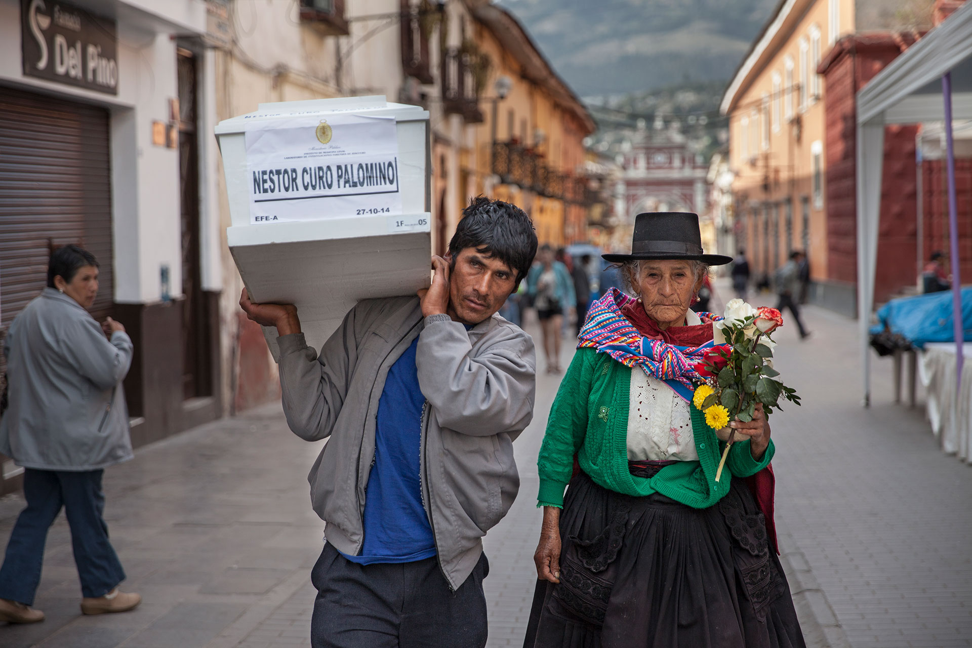 Eusebia Palomino recorre la ciudad de Huamanga escoltando el féretro que contiene los restos de su hijo, Néstor Curo Palomino, asesinado en 1990 por Sendero Luminoso cuando defendía a su pueblo de un ataque terrorista. Ella lo lleva al poblado de Huallhua, distante a 12 horas en carro.