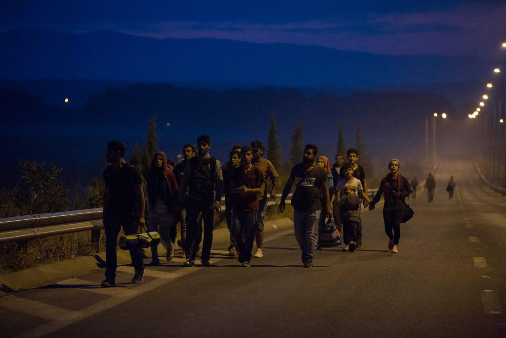 Refugees walk along a road at dawn in Idomeni, Greece, heading towards the border with Macedonia, located a few kilometers away. (Idomeni, Greece. 08/25/2015).