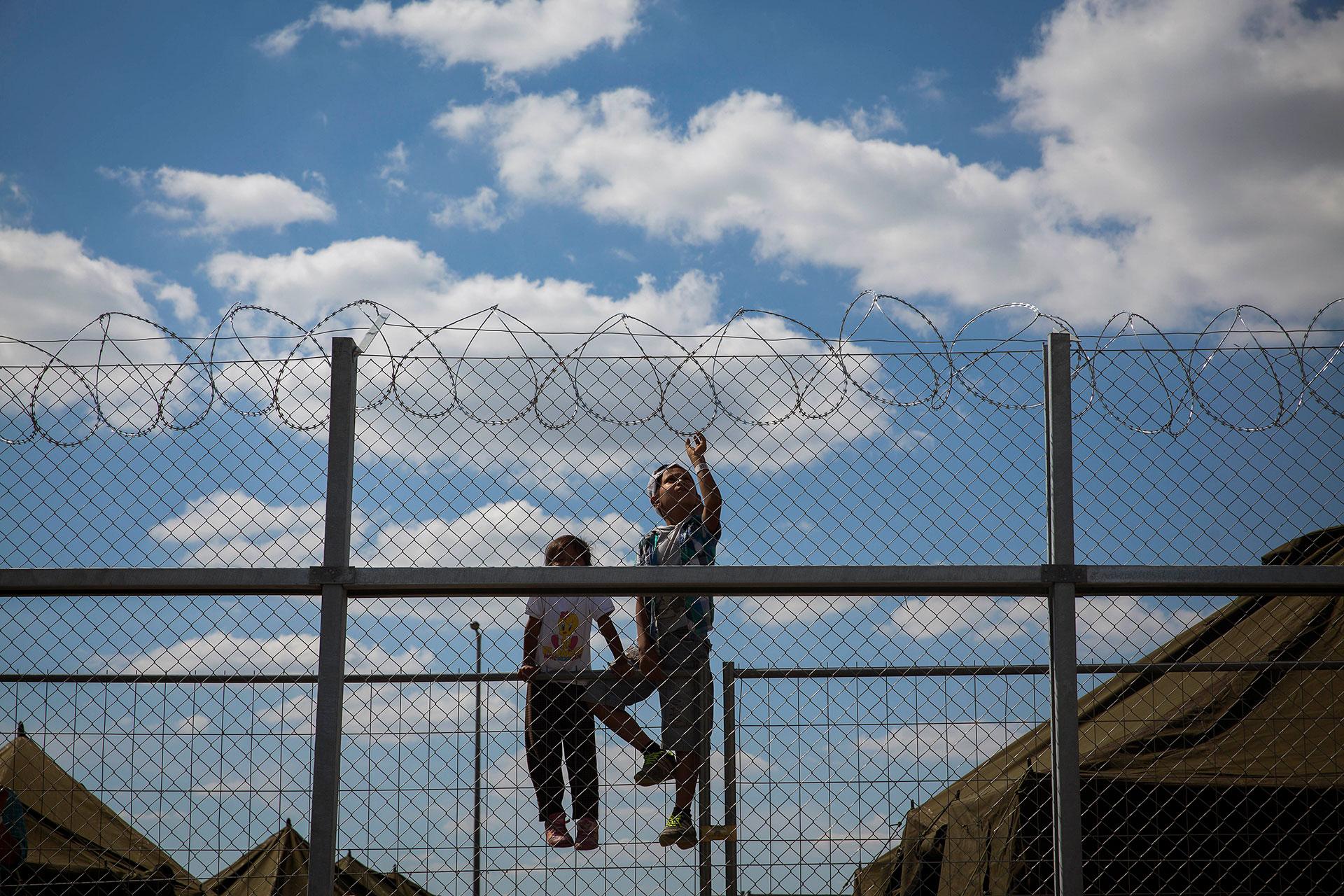 Un niño y una niña subidos a una valla en el interior del campo de personas refugiadas de Roszke. El Gobierno húngaro dirigía a todos los personas recién llegadas a campos similares, donde podían permanecer días encerrados mientras les identificaban y les dejaban continuar su camino. (Roszke. Hungría. 09/09/2015).