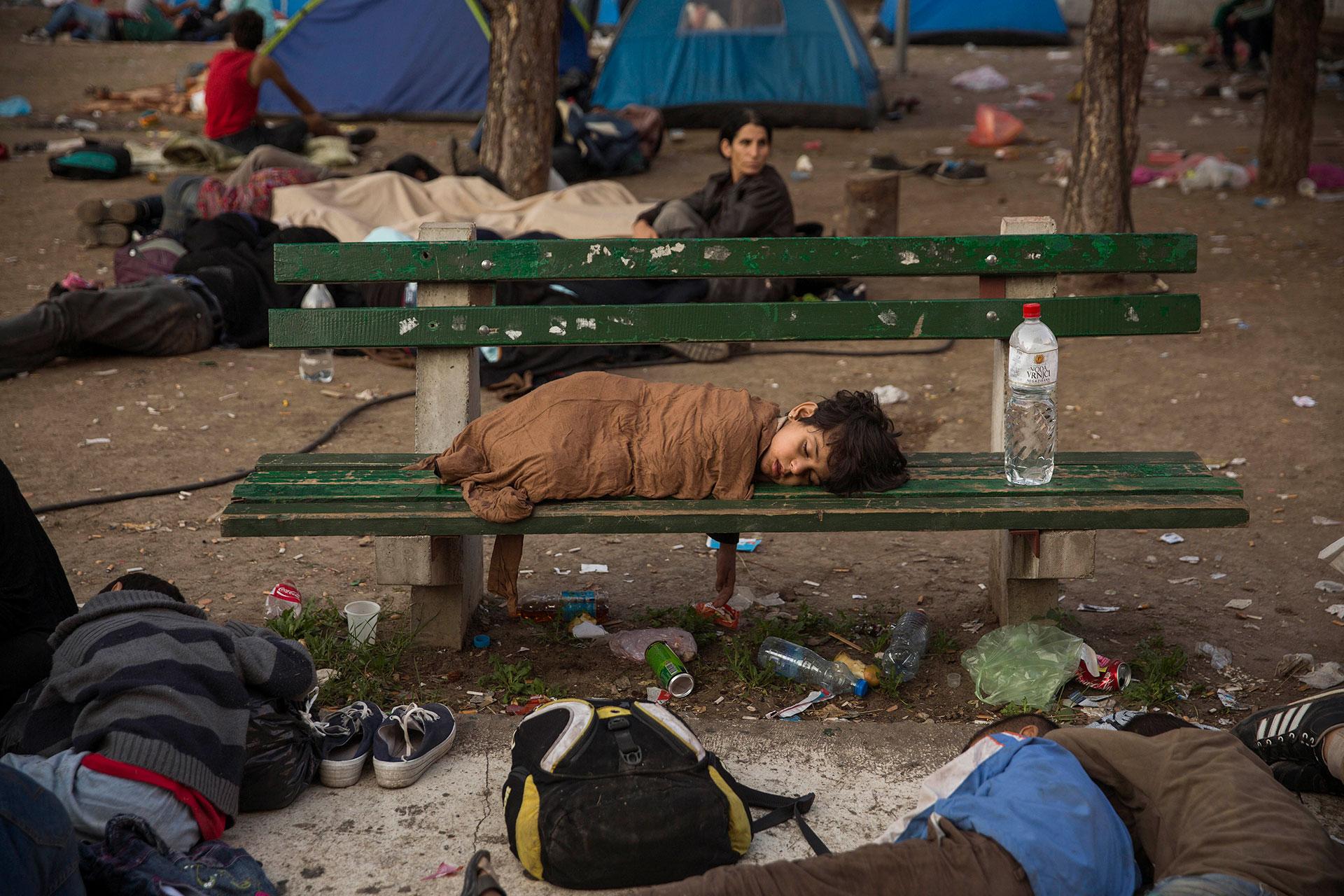 Un niño duerme en un banco del parque Bristol de Belgrado. Ese parque era donde pasaban la noche cientos de refugiados y refugiadas antes de continuar su camino hacia Hungría. (Belgrado, Serbia. 30/08/2015).