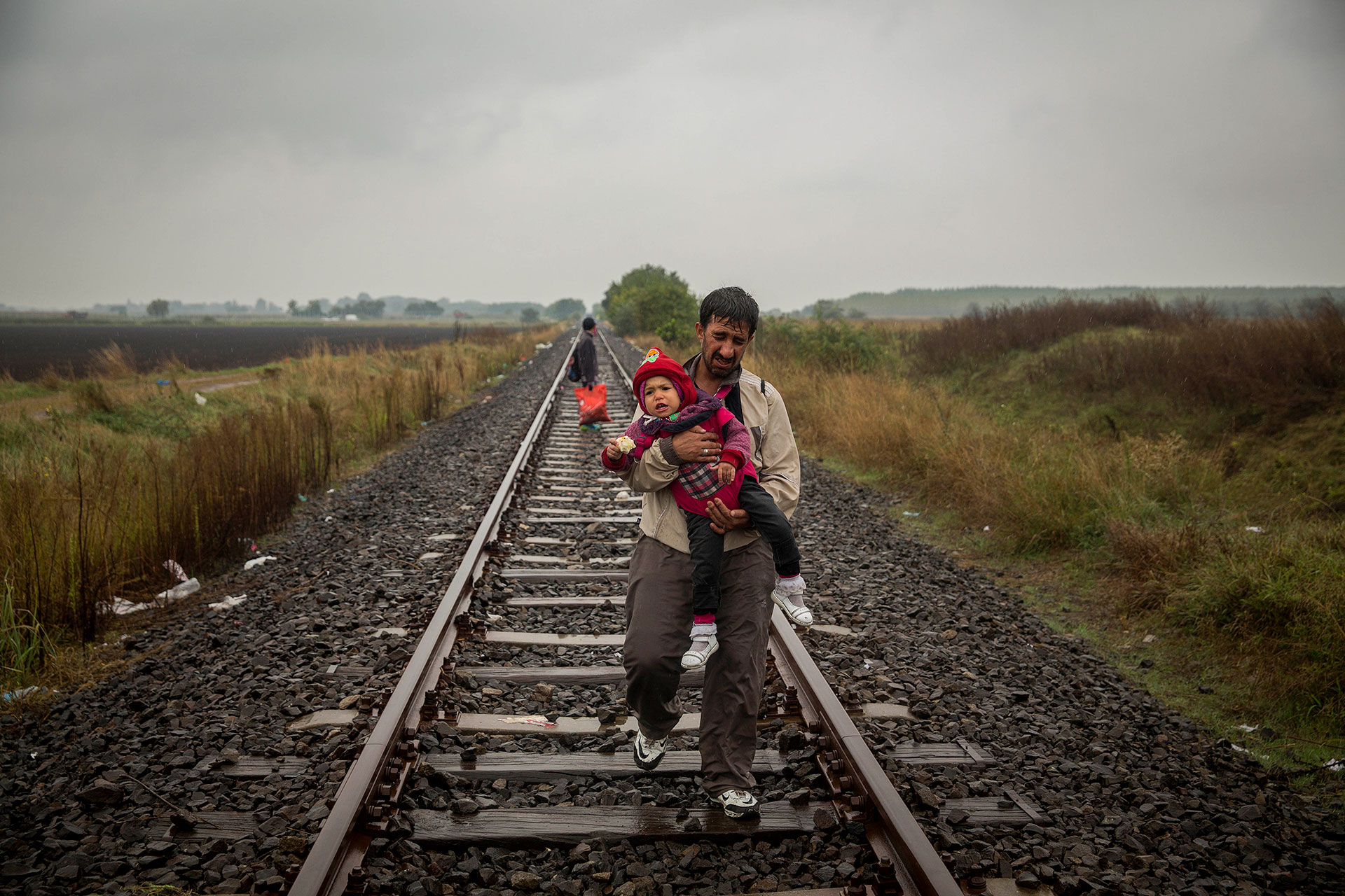 A father walks along the railroad tracks carrying his kid in his arms after having crossed the border between Serbia and Hungary. He is entering Roszke. (Roszke, Hungary. 10/09/2015).