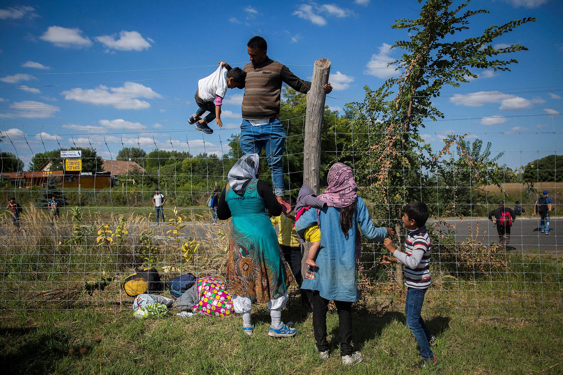 Una familia salta la valla de una autopista en el pueblo de Roszke junto a cientos de personas, huyendo de la policía que quería llevarlos a un centro de identificación. (Roszke. Hungría. 09/09/2015).