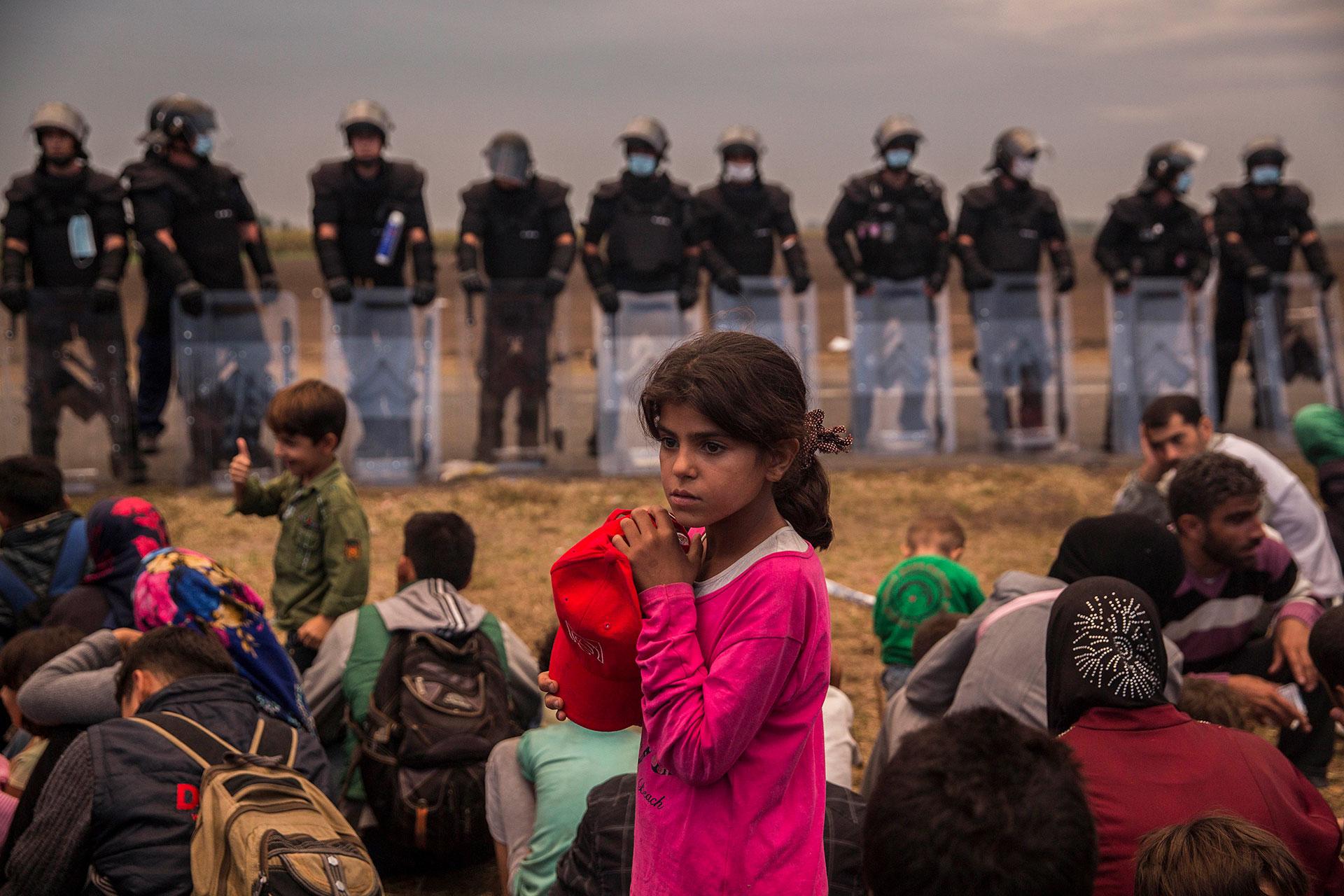 Una niña espera a ser trasladada a un campo de refugiados y refugiadas, junto a cientos de personas en el punto de recepción de Roszke, fronterizo con Serbia. (Roszke. Hungría. 05/09/2015).