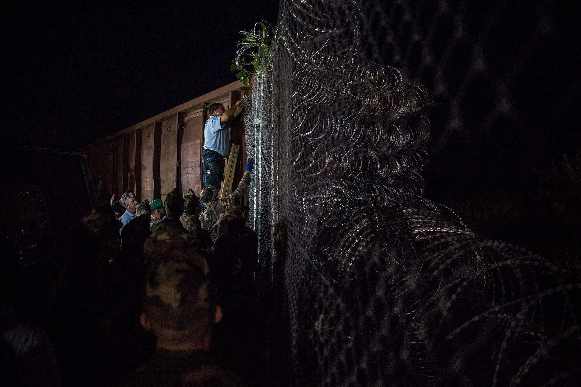 Policías y soldados húngaros terminan de colocar la valla en el paso fronterizo de Roszke, por donde entraban las personas refugiadas al país. (Roszke. Hungría. 14/09/2015).