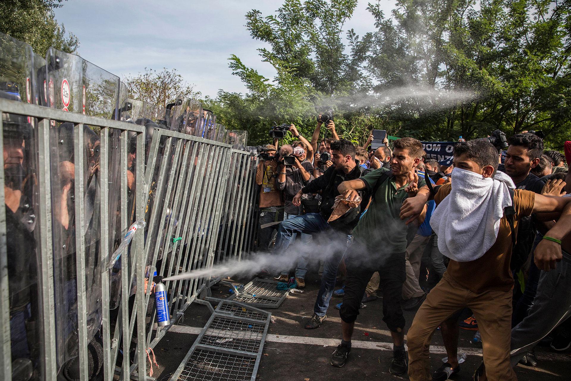 Policías húngaros lanzan gas pimienta a las personas que intentan pasar la frontera desde Serbia después de pasar dos días bloqueados sin poder continuar su camino. (Horgos. Serbia. 16/09/2015).