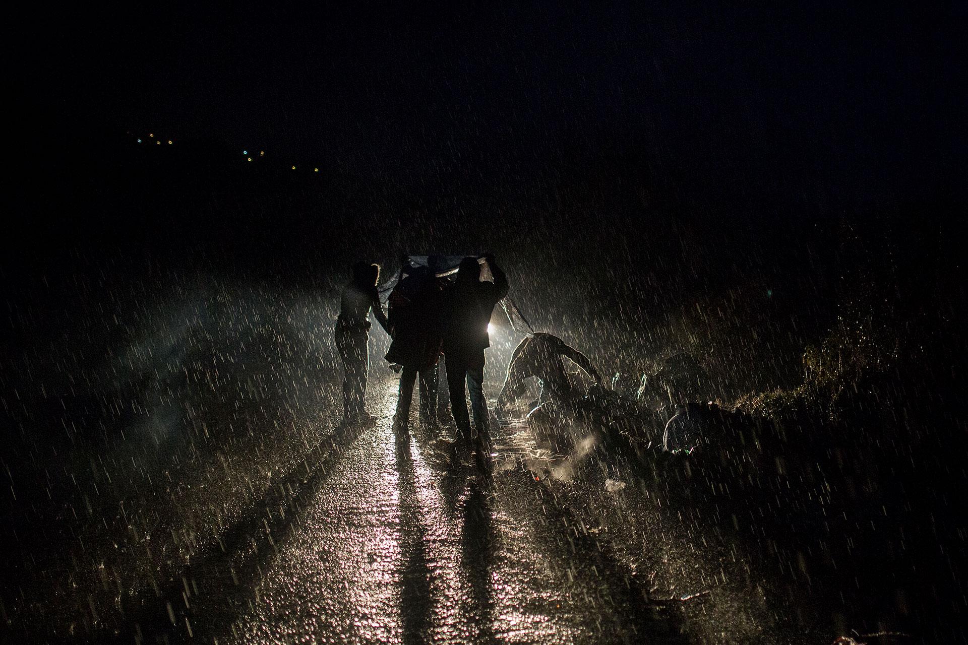 Un grupo de personas refugiadas pasa la noche bajo una intensa lluvia, a la espera de que algún vehículo les ayude a trasladarse desde el norte de la isla a los puntos de recepción ubicados a más de 60 kilómetros.
