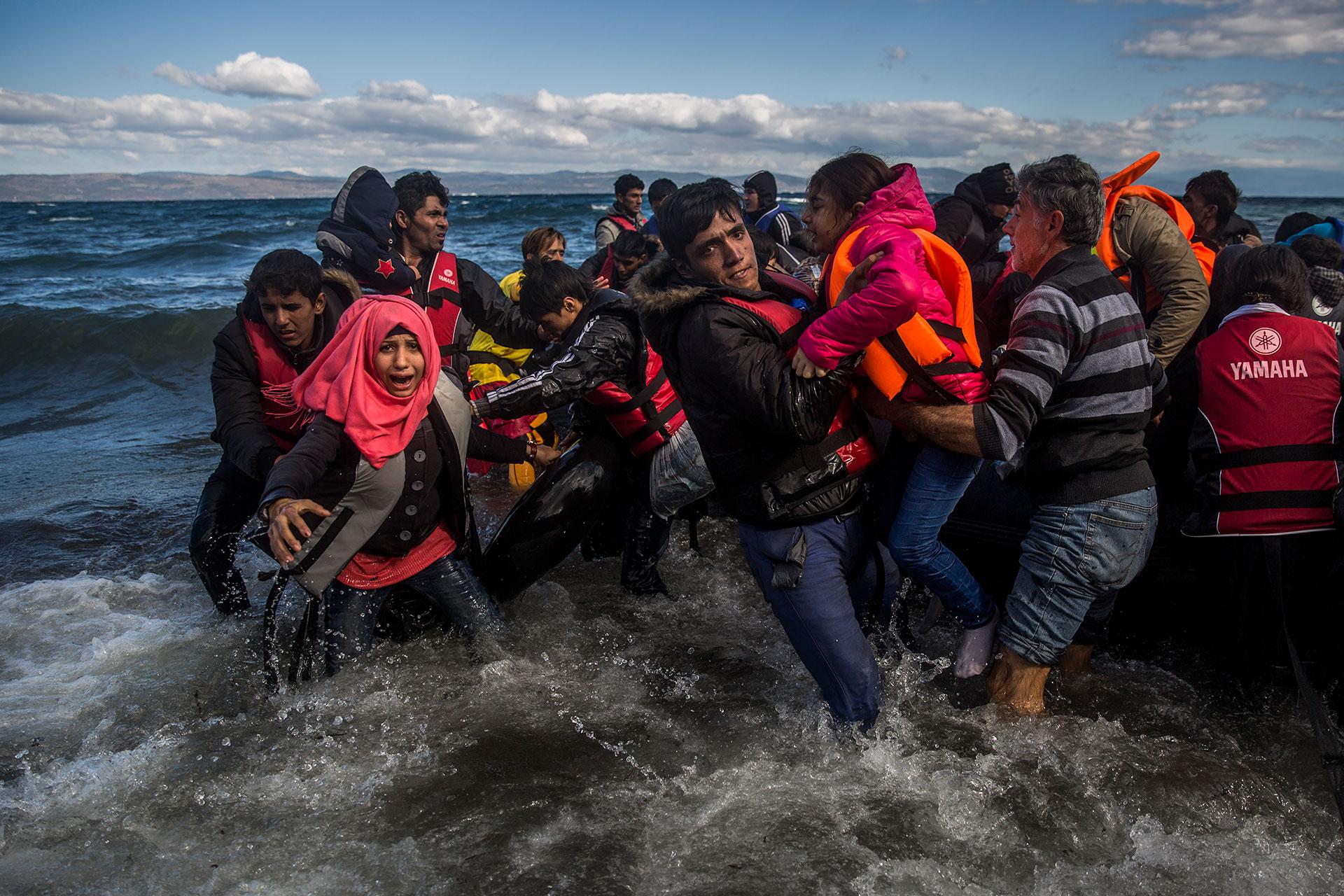 Personas refugiadas de origen afgano y sirio desembarcan en la isla griega de Lesbos.