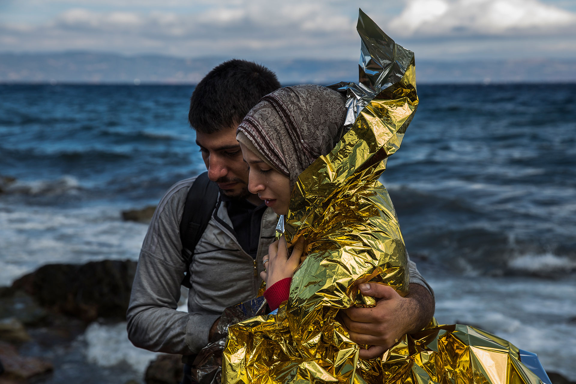 A couple of Syrian youths leave the beach where they've just landed on the Greek island of Lesbos, coming from the coasts of Turkey
