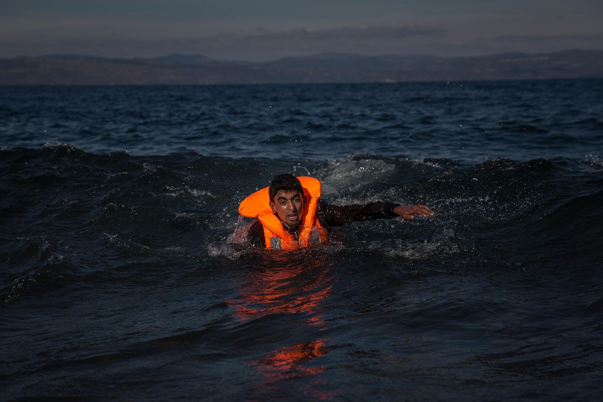 Un joven nada hacia la orilla de una playa en la isla griega de Lesbos tras saltar de la precaria embarcación en la que, junto a otras decenas de personas, han cruzado los 10 kilómetros de mar que separan la isla de las costas turcas.