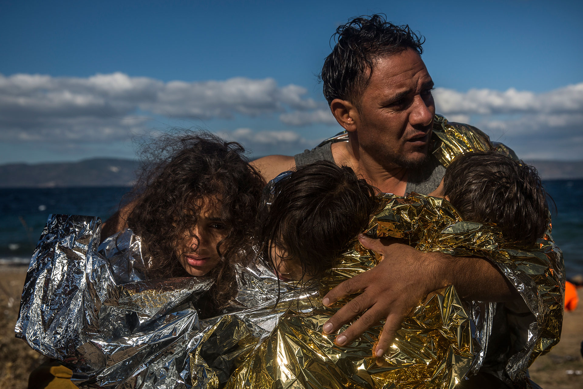 A father hugs his children, wrapped in thermal blankets, just before landing on a beach in Lesbos, coming from the coasts of Turkey.