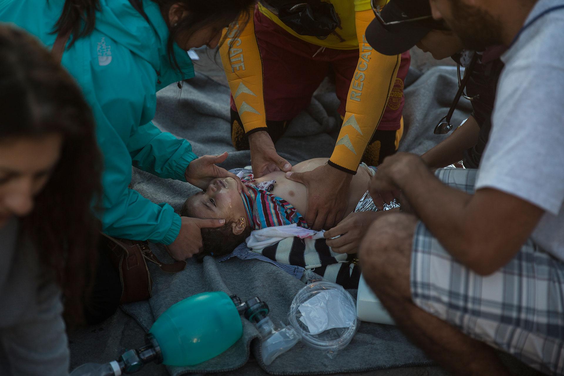 Personal médico y paramédico trata de reanimar a un bebé que pasó más de una hora en el agua, después de que el barco en el que viajaba junto a otras 300 personas naufragara entre Turquía y Lesbos.