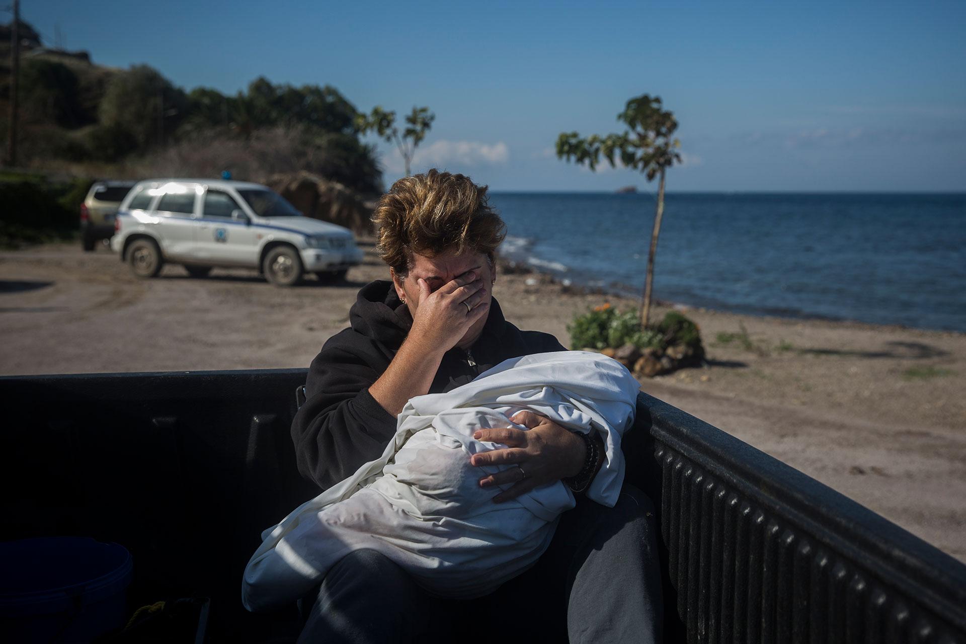 Una vecina del pueblo de Petra (Lesbos) llora mientras sujeta el cadáver de un bebé que apareció en las playas cercanas al municipio.