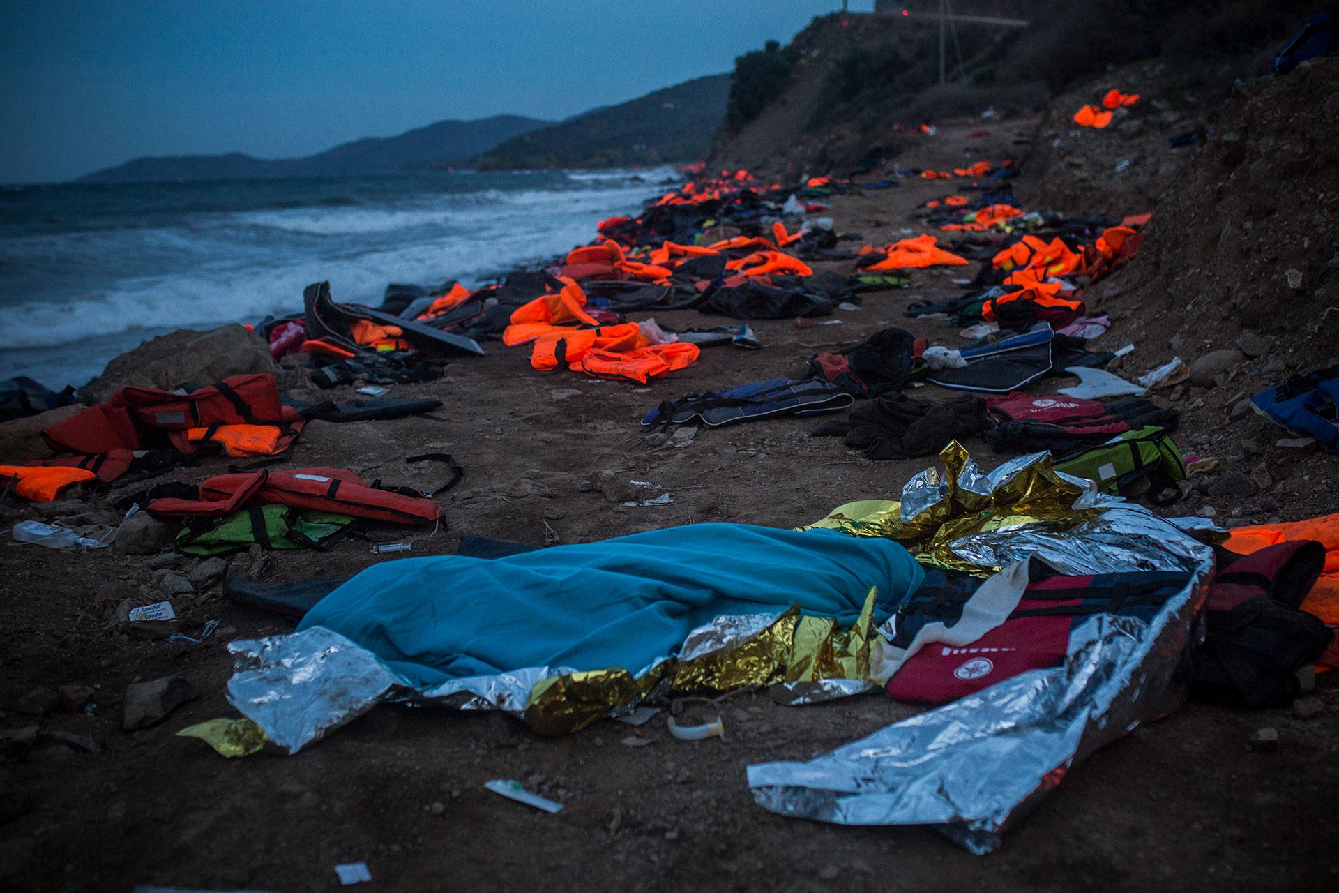 El cadáver de un joven afgano de 20 años permanece envuelto en una manta, en una playa de Lesbos, minutos después de que un grupo de médicos y socorristas voluntarios y voluntarias trataran de salvarle la vida tras rescatarle del agua, sin conseguirlo.