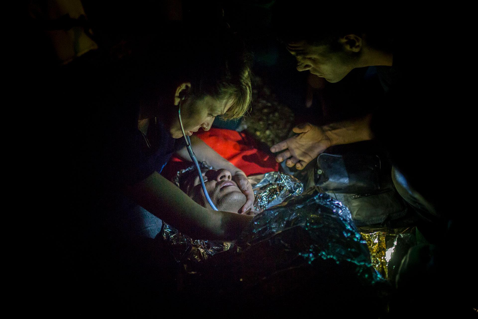 Personal sanitario voluntario trata la hipotermia de un joven poco después de su llegada a la isla de Lesbos, procedente de las costas turcas.