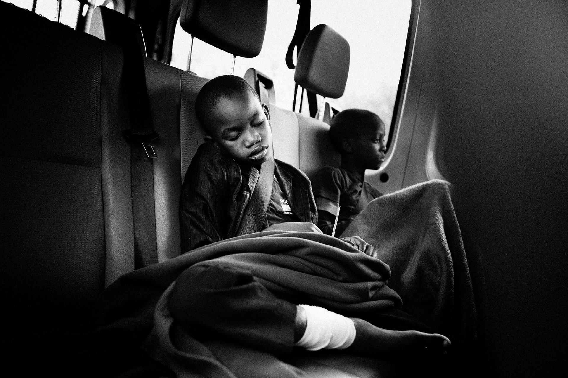 De camino del aeropuerto al hospital, Beto sucumbe al cansancio. Han transcurrido más de 24 horas desde que su padre y su madre le vistieron con sus mejores ropas y le entregaron a los socios locales de Peace Village en Luanda, Angola.
