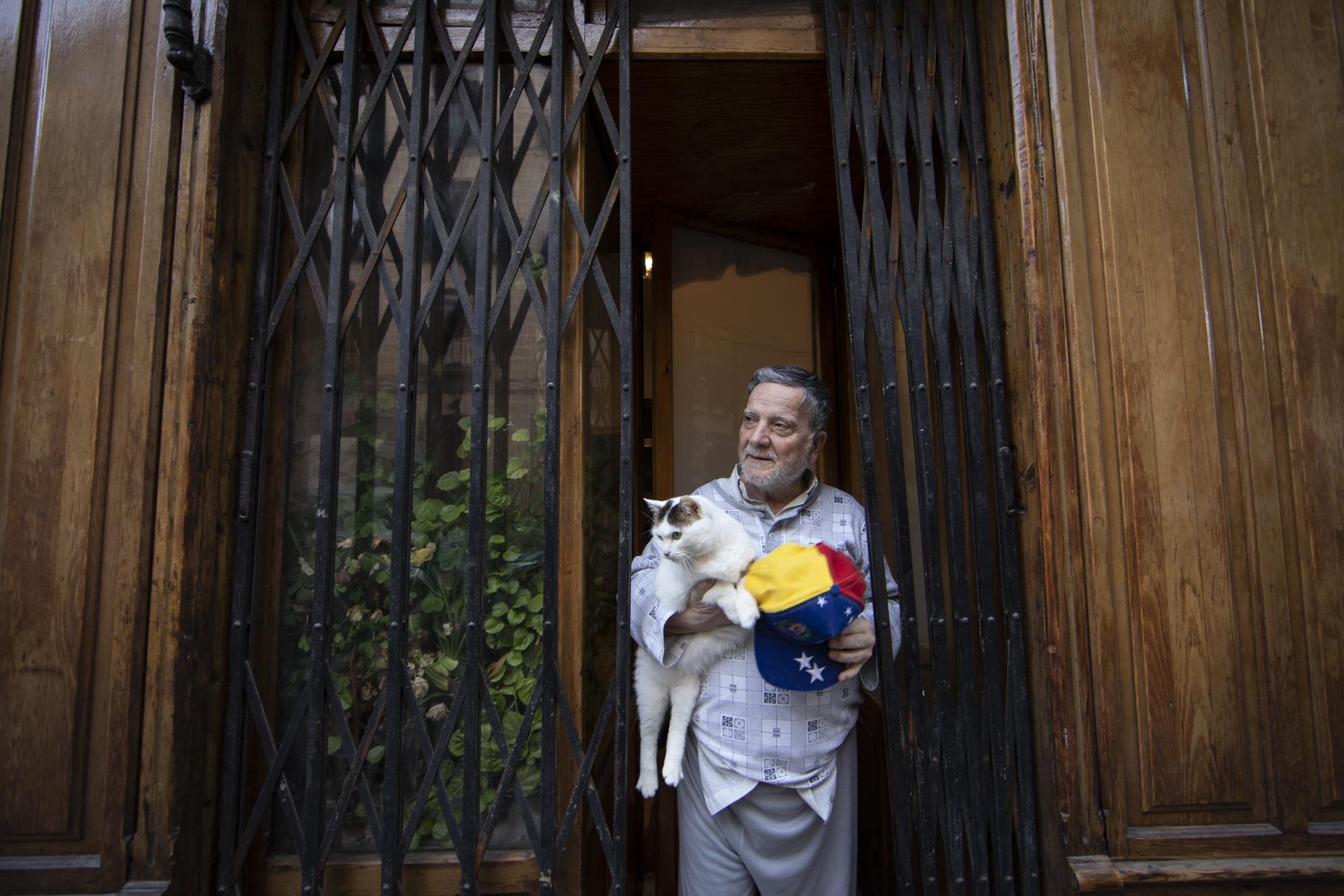 """Manolo (75) nació en Trujillo, pero lleva sesenta años viviendo en Madrid. Ha dedicado su vida a la enseñanza y ahora, jubilado, vive en un peculiar bajo de Lavapiés rodeado de secadores vintage y lavacabezas. El que es ahora su hogar, fue una peluquería histórica, y está protegida por Patrimonio, así que debe conservarse tal y como estaba. En la peluquería habitan también su mujer, su tía y su gata República Socialista, que no para de maullar durante toda la entrevista. Y es que Manolo ha reivindicado siempre sus ideales, incluso a la hora de bautizar a su amiga de cuatro patas, que por cierto es la gata más famosa del barrio. Ahora que ha pasado lo peor del Covid-19, Manolo sólo quiere """"seguir con su vida de lucha"""", como ha hecho siempre. Esa era su antigua normalidad y será la nueva también."""