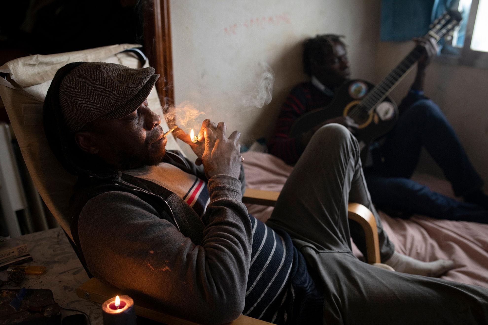 Yusuf (50) y Bruno (50) son de Guinea Bissau. Llegaron a Madrid hace más de veinte años, y viven en un pequeño piso okupado de Lavapiés. Yusuf era futbolista profesional, pero ahora se gana la vida tocando la guitarra en la calle. Bruno es hostelero, pero también vive de la música callejera. Ahora no pueden hacerlo, porque están respetando el confinamiento por el Covid-19, así que no perciben ningún tipo de ingreso. Les han cortado el agua también, y tienen que salir a los baños públicos cada vez que lo necesitan. Con los bares cerrados, tienen pocas opciones. Lo más duro de la cuarentena para ellos es... pasar hambre. El cansancio psicológico también va haciendo mella, y no poder comunicarse con nadie lo empeora todo. Echan de menos a la familia, a los amigos, la vida normal. Quizás no nos damos cuenta de lo afortunados que somos la mayoría. Quizás este es un buen momento para hacerlo.
