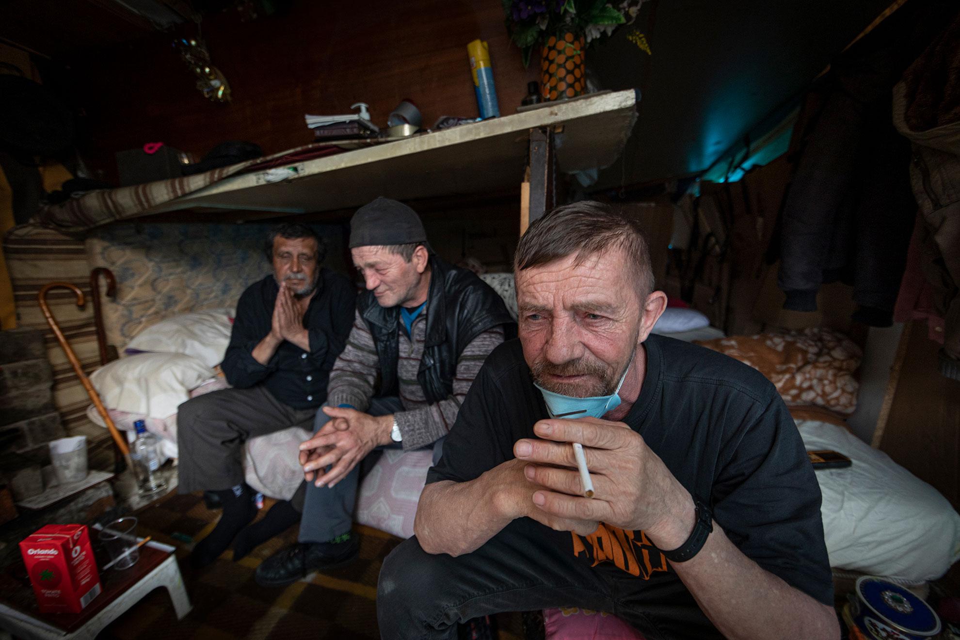 """Dor, Nelu y Gigi son de Rumanía. Llegaron a Madrid hace 20 años y hoy pasan el confinamiento en una chabola pegada a la M-30. A pesar de vivir en la calle, antes del Covid-19 tenían trabajos esporádicos en la construcción. Ahora sólo tienen el subsidio de Nelu, que apenas alcanza para comprar comida todo el mes. Ni siquiera pueden pedir en los semáforos, porque la policía les pidió que no salieran de casa hasta que se levantase el Estado de Alarma. """"Tiene que ser así, lo entendemos, es la ley"""", dicen resignados. Juegan al dominó para pasar el rato, sobre una tabla que utilizan a modo de mesa, y con el calor de una plancha de ropa preparan café. A pesar de que la ciudad está desierta y apenas circulan coches, cada vez que pasa uno retumba como si estuviera dentro de la infravivienda, hecha de tablones de madera y plásticos. Es difícil imaginar cómo era vivir ahí un día cualquiera, con la M-30 rugiendo en hora punta, antes del confinamiento."""